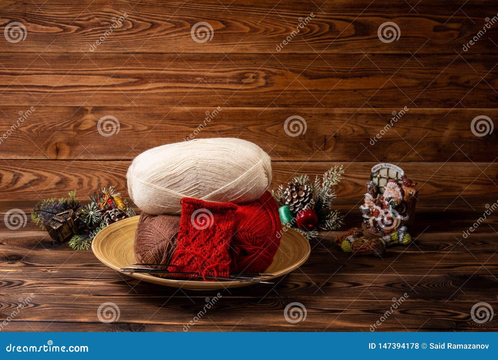 Boules colorées rouges et blanches de fil, d aiguilles de tricotage et de jouets de Noël sur le fond en bois