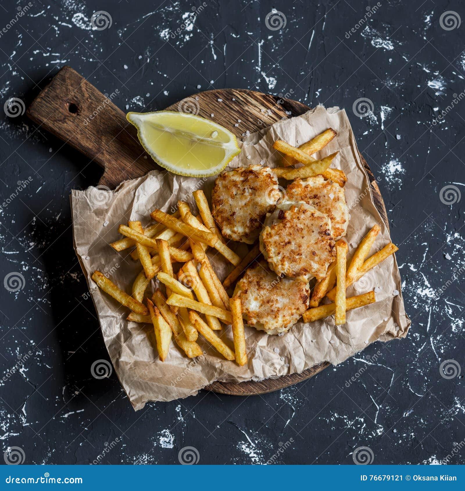 Boules de poissons et pommes chips sur la planche à découper rustique sur un fond foncé