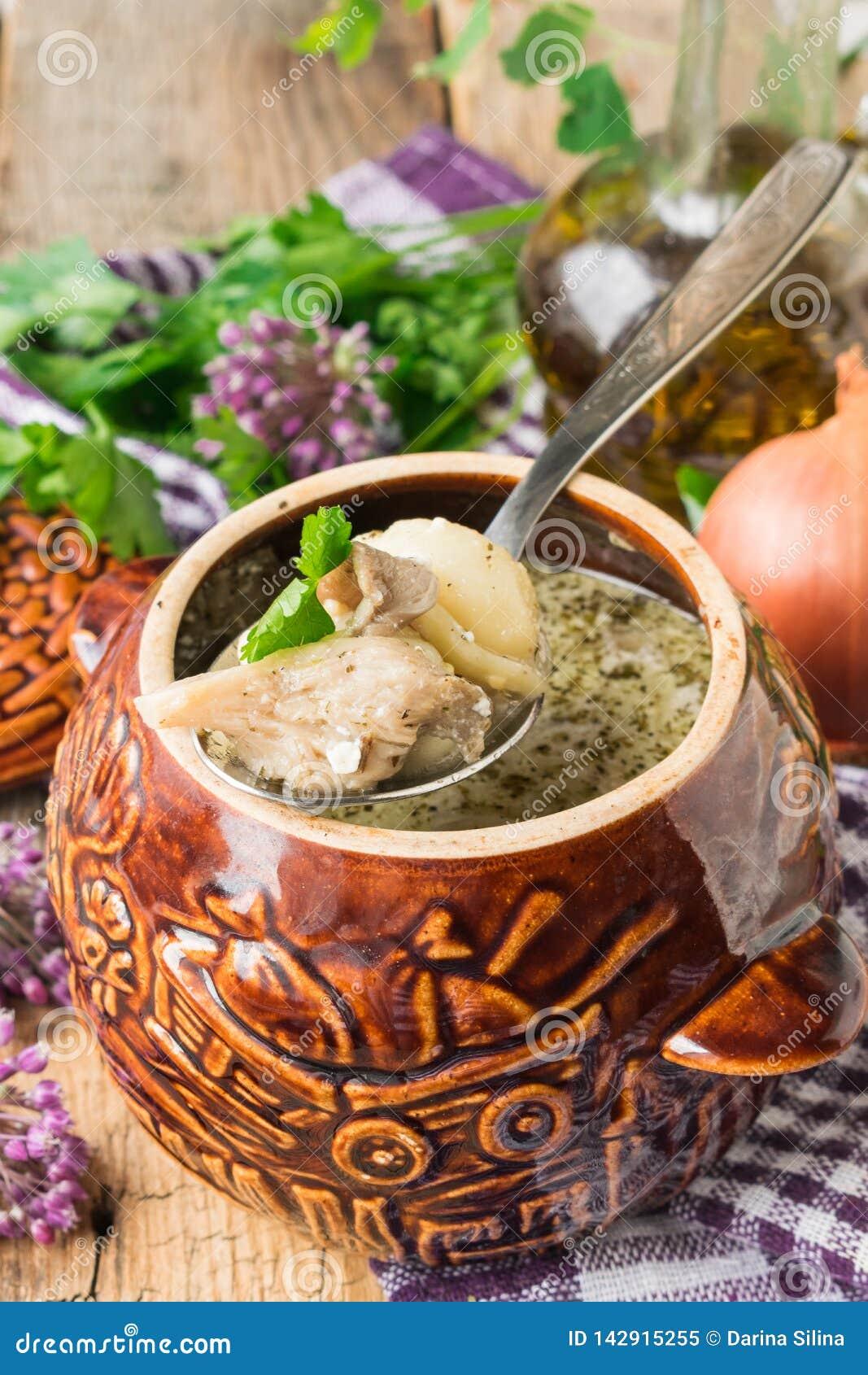 Boulettes faites maison avec des champignons cuits au four dans un pot en céramique dans le four