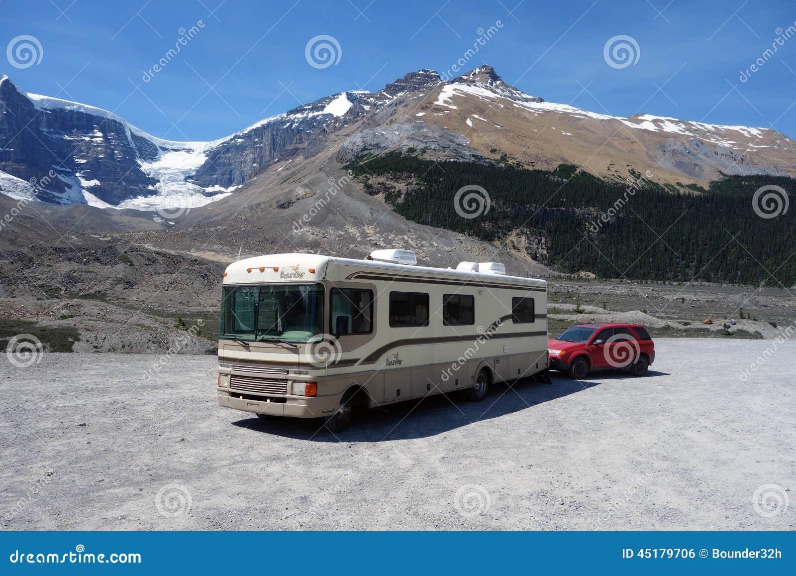 Bounder и шлюпка припарковали с скалистыми горами на заднем плане