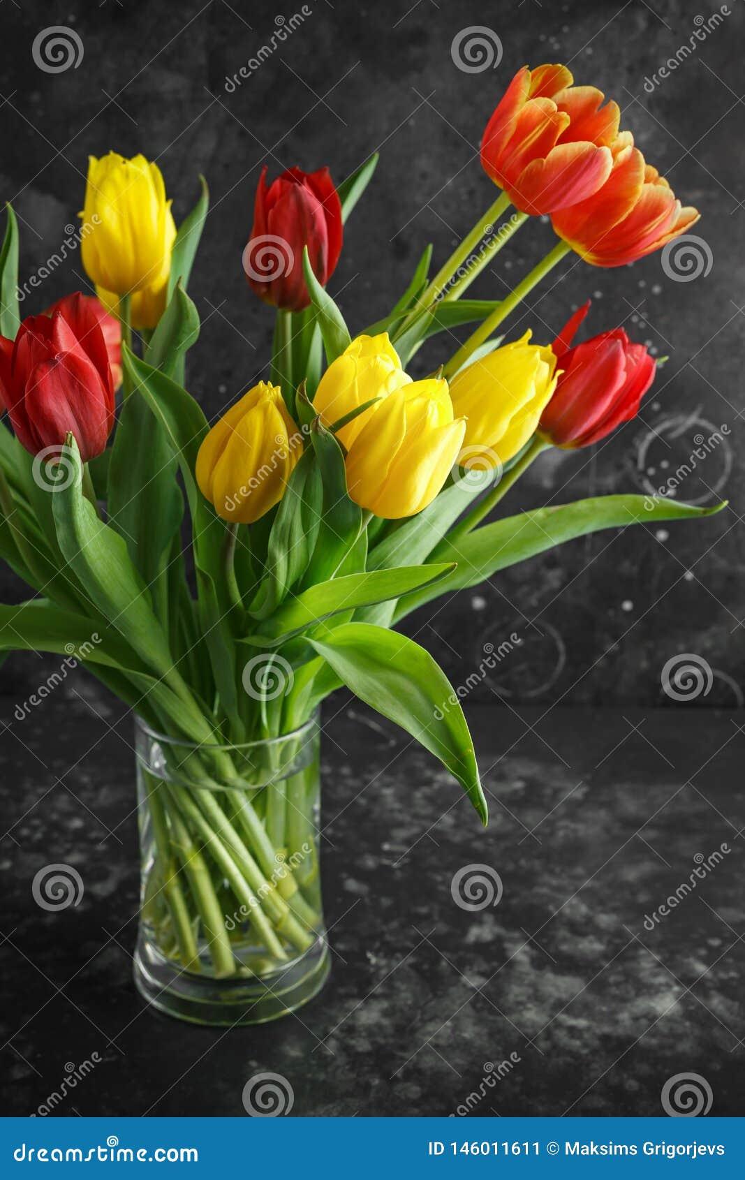 Bouqet romântico das tulipas no fundo escuro rústico