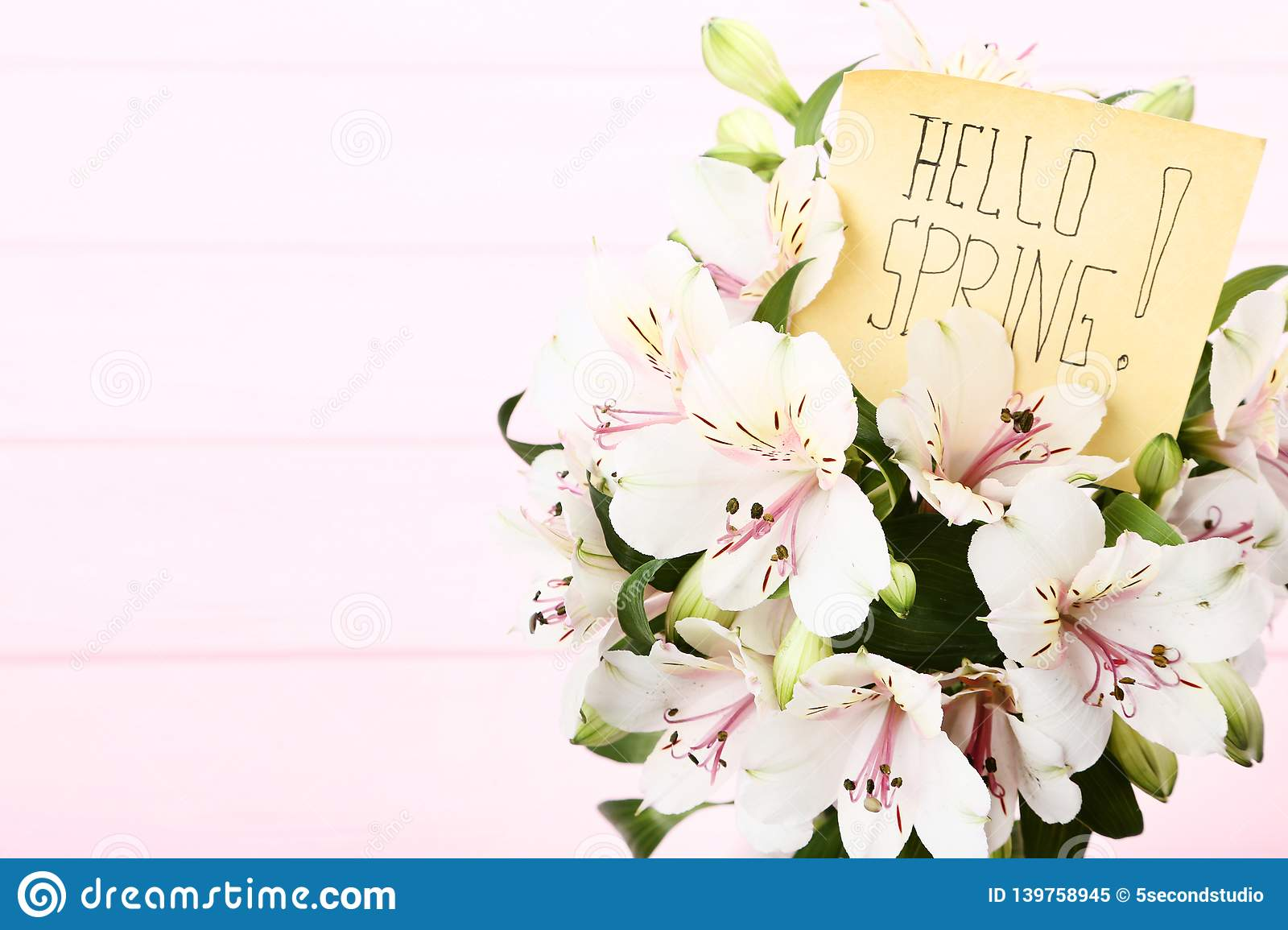 Bouquet of alstroemeria flowers with text Hello Spring on wooden background royalty free stock photo