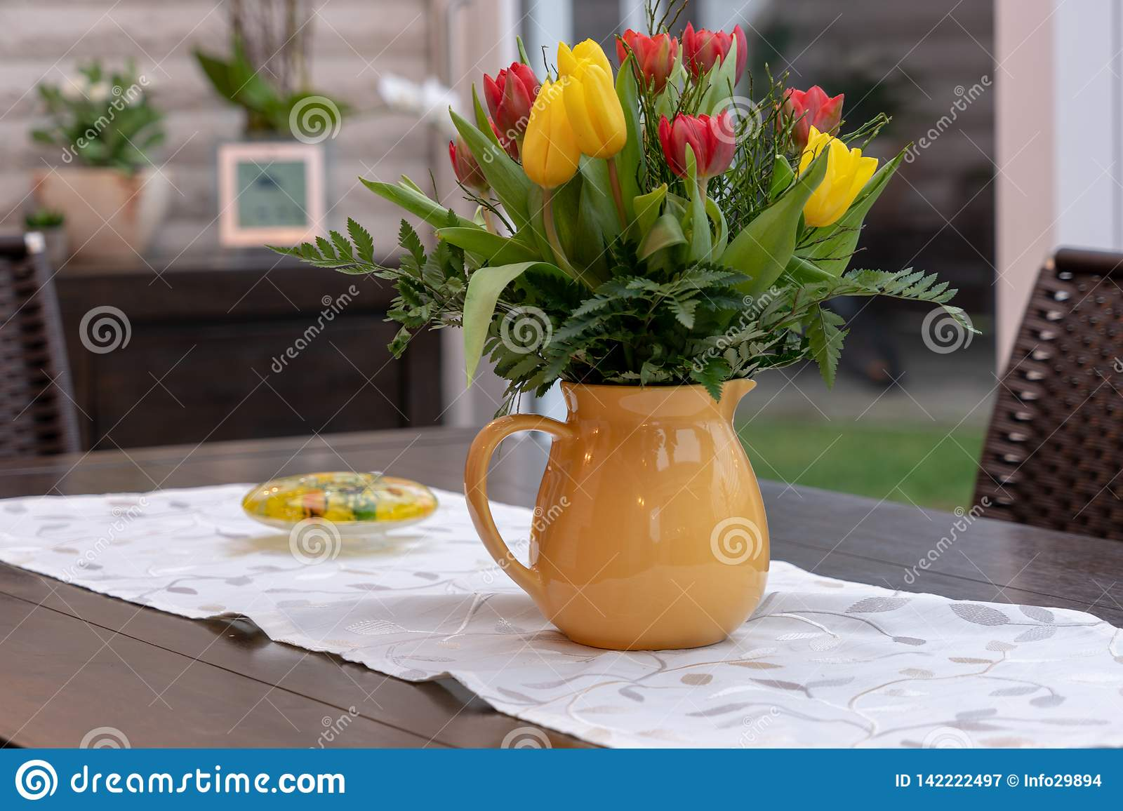 bouquet of colourful tulips stands in a yellow vase