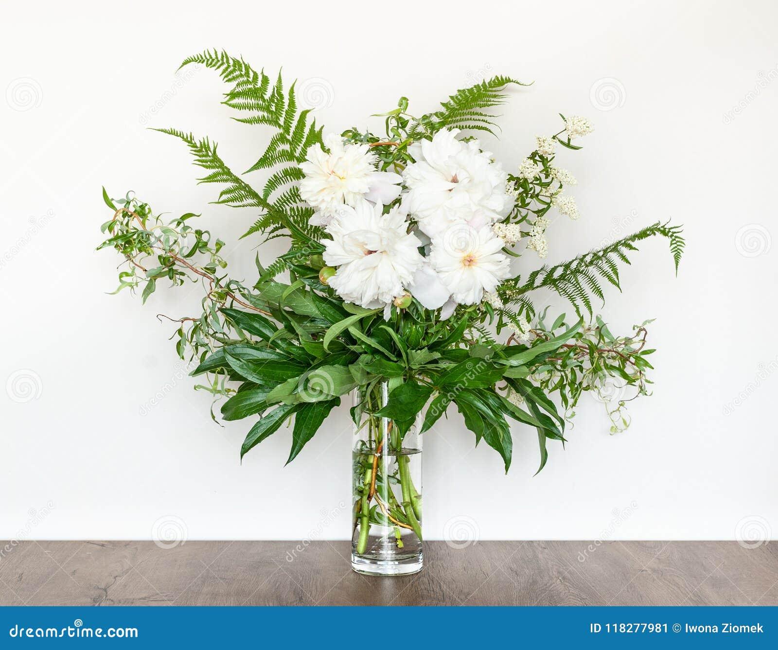 Bouquet décoratif des pivoines blanches dans un vase en verre