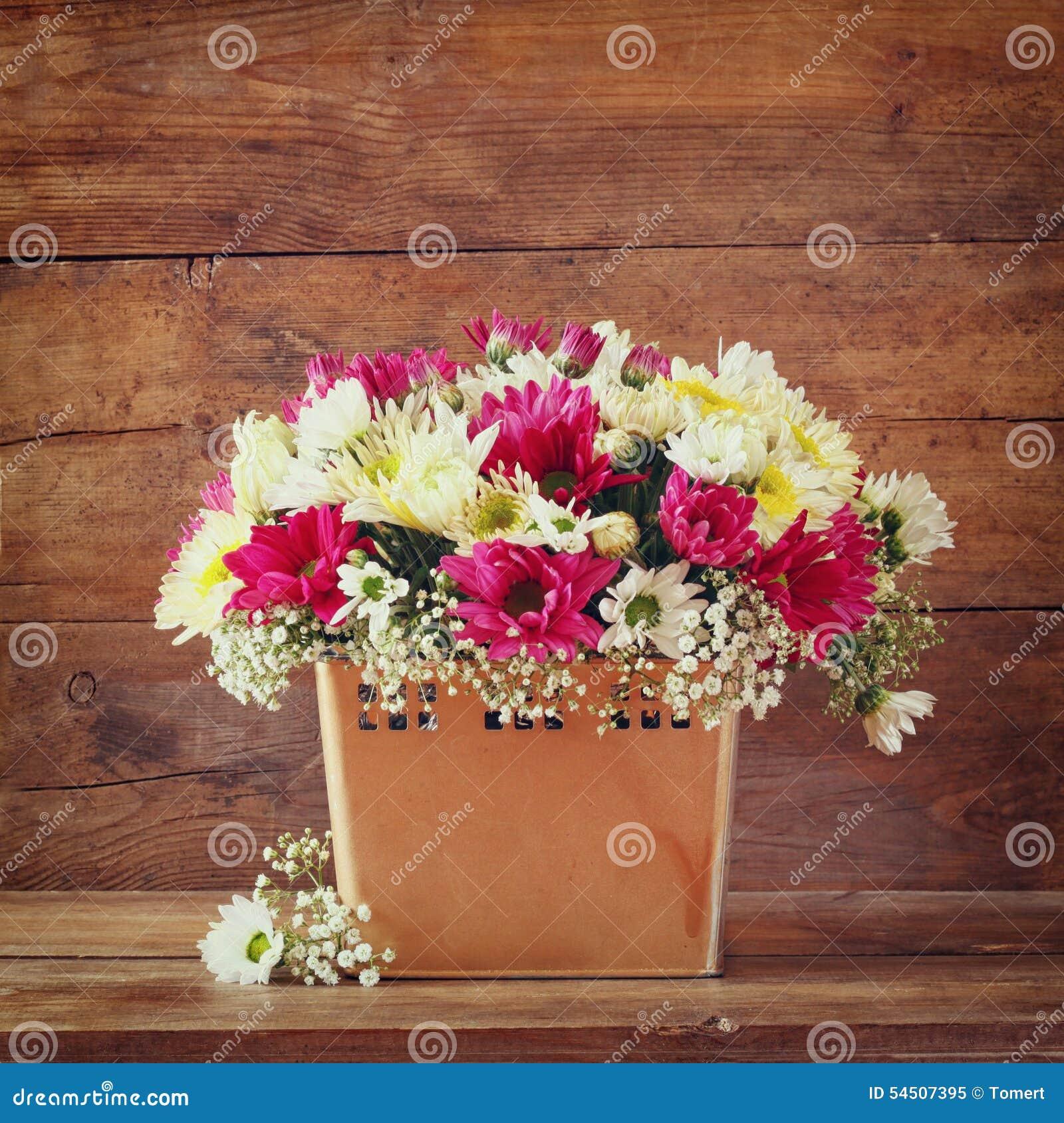 Bouquet d été des fleurs et sur la table en bois avec le fond en bois image filtrée par vintage