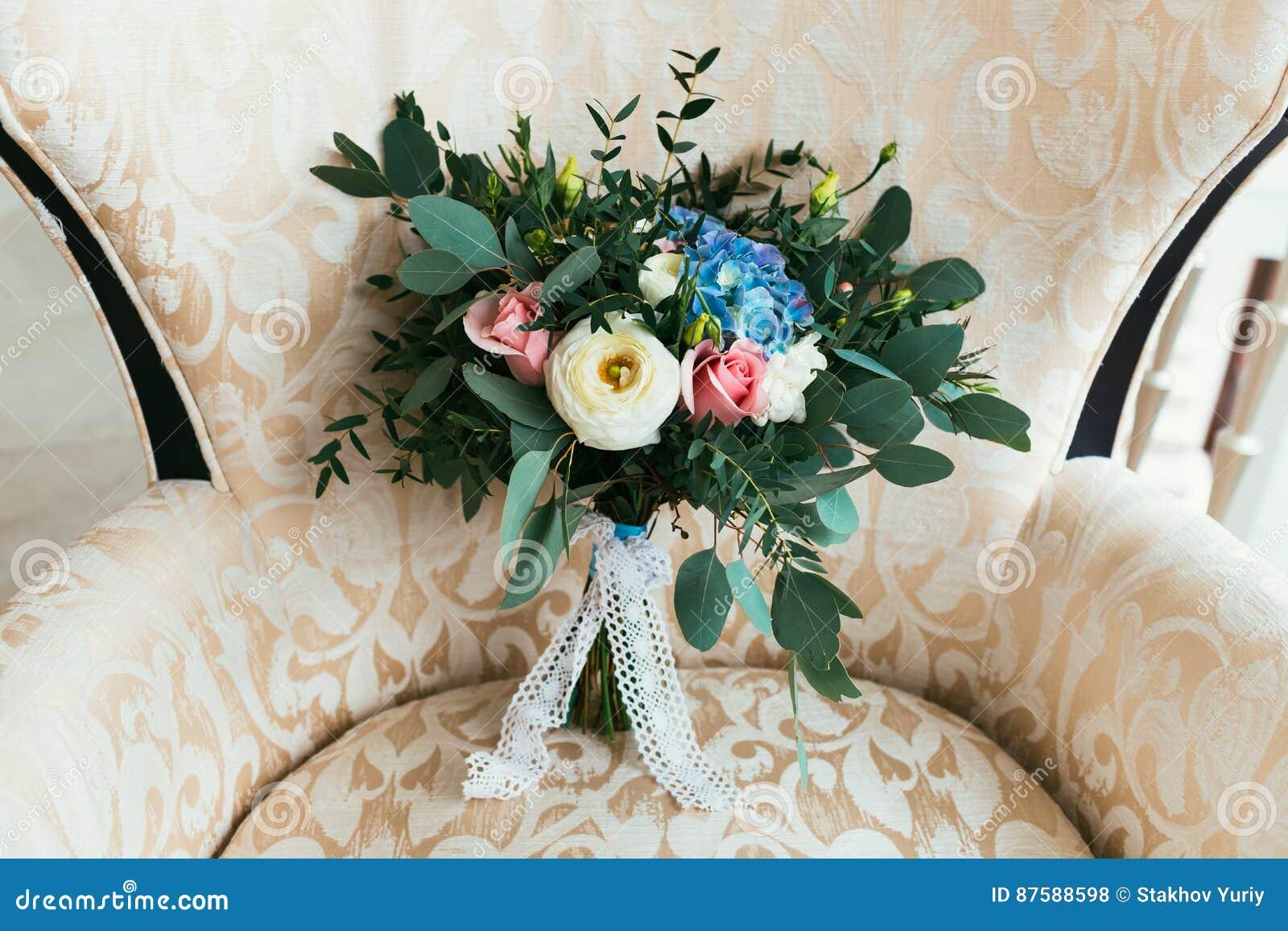 Bouquet de mariage des fleurs fraîches pour la jeune mariée se tenant sur le fauteuil