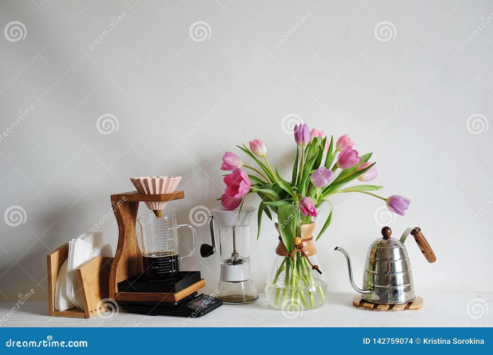 Bouquet de tulipes de fleurs dans le décanteur de café sur la table blanche Brassage manuel avec l origami dispositif d écoulemen