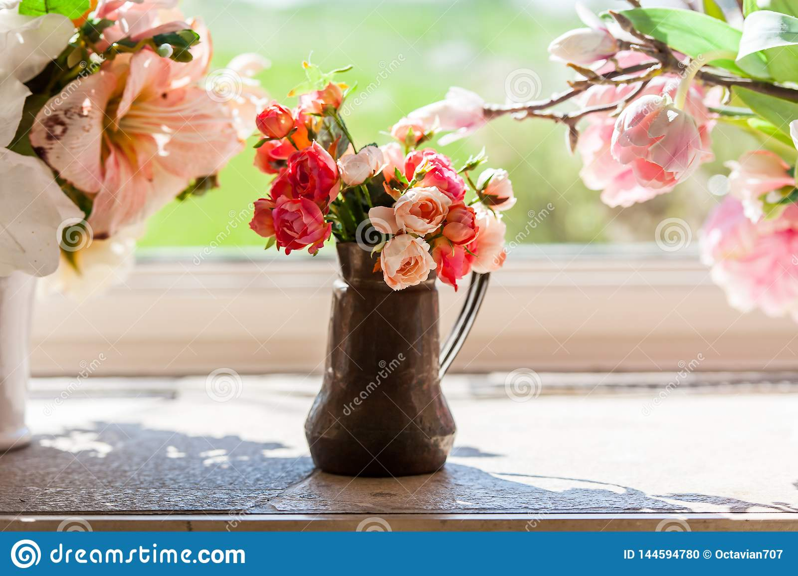 Bouquet des fleurs dans un vase devant la fenêtre