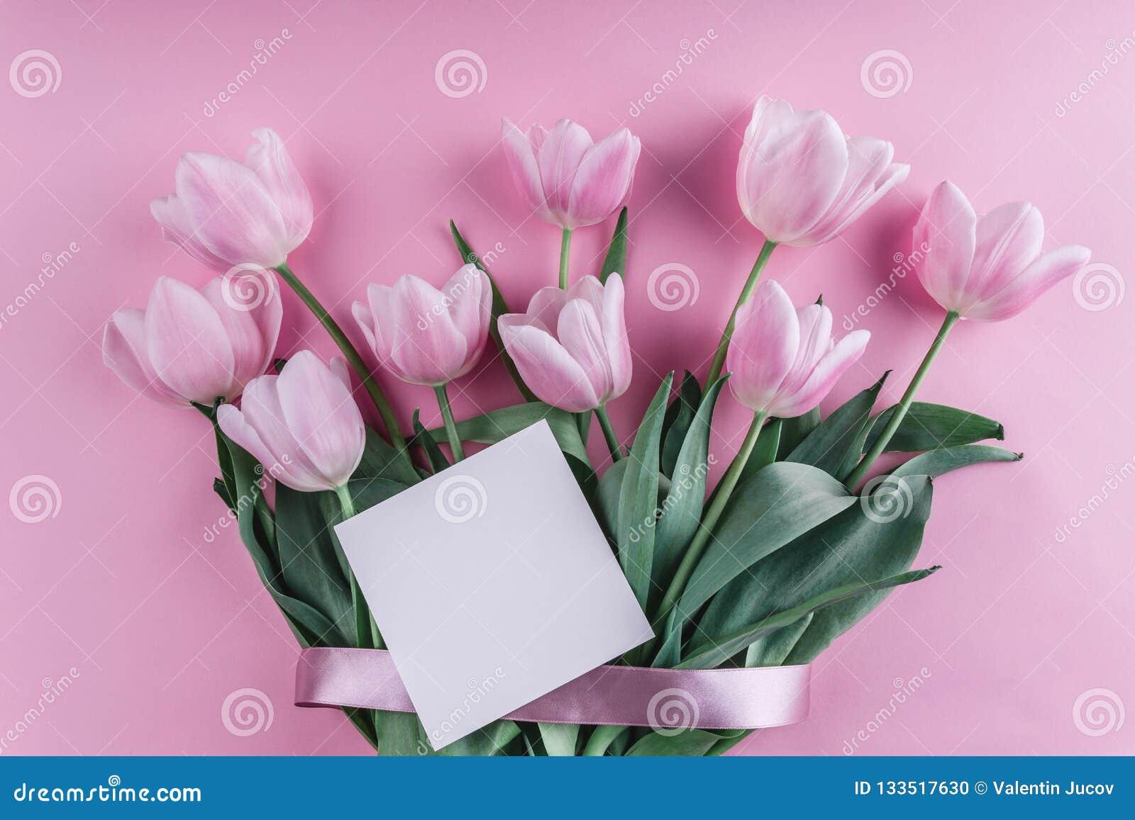Bouquet des fleurs de tulipes et de la feuille de papier blanches au-dessus de fond rose-clair Carte de voeux ou invitation de ma