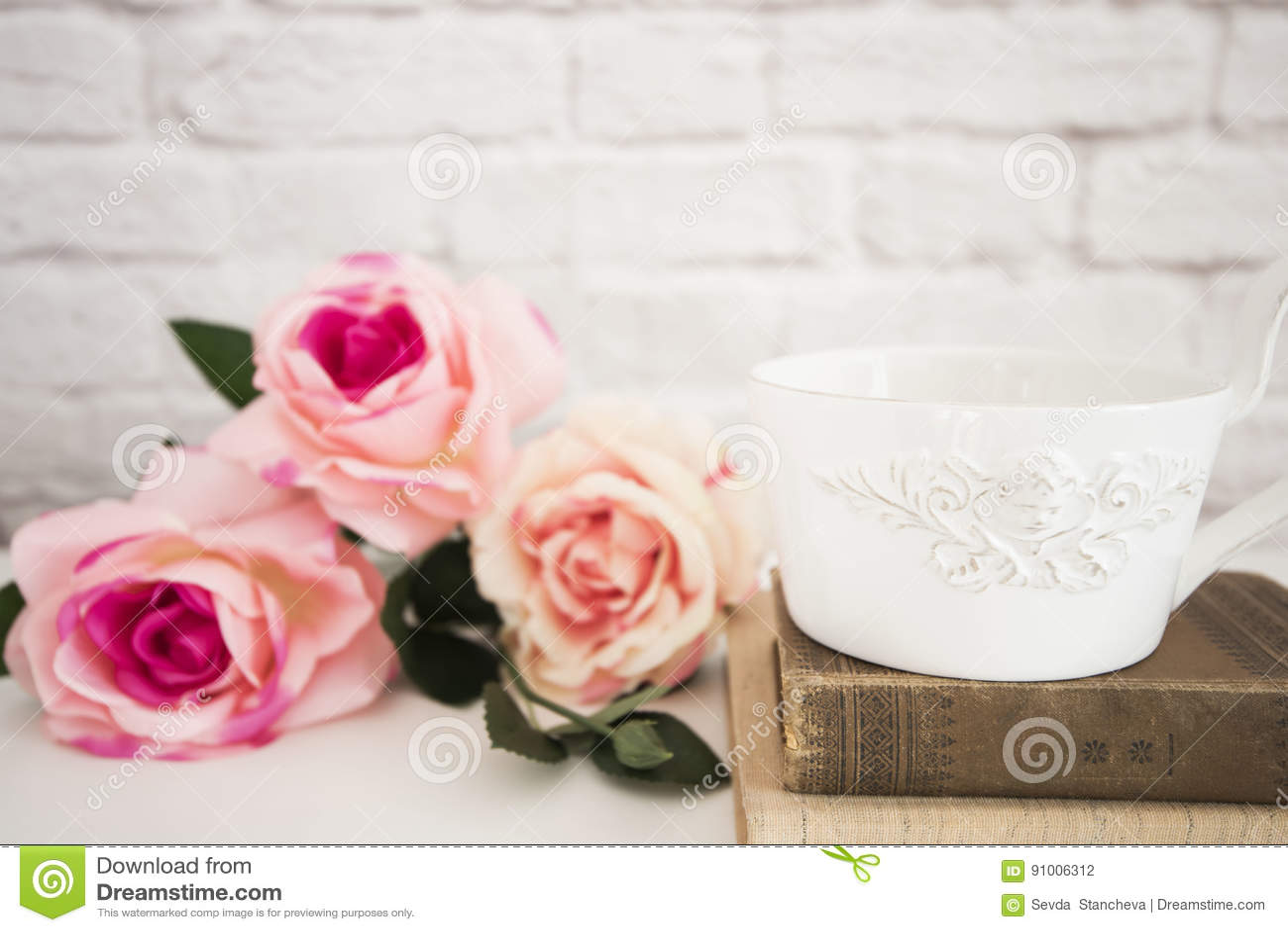 Bouquet des roses sur un bureau blanc a grande tasse de café au