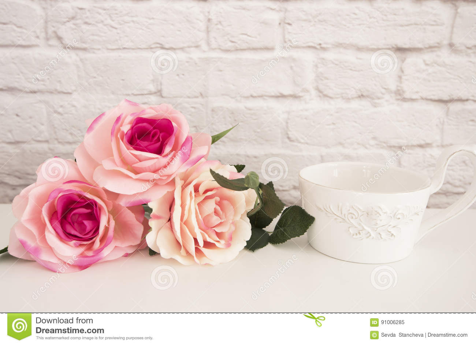 Bouquet des roses sur un bureau blanc a grande tasse de café dans