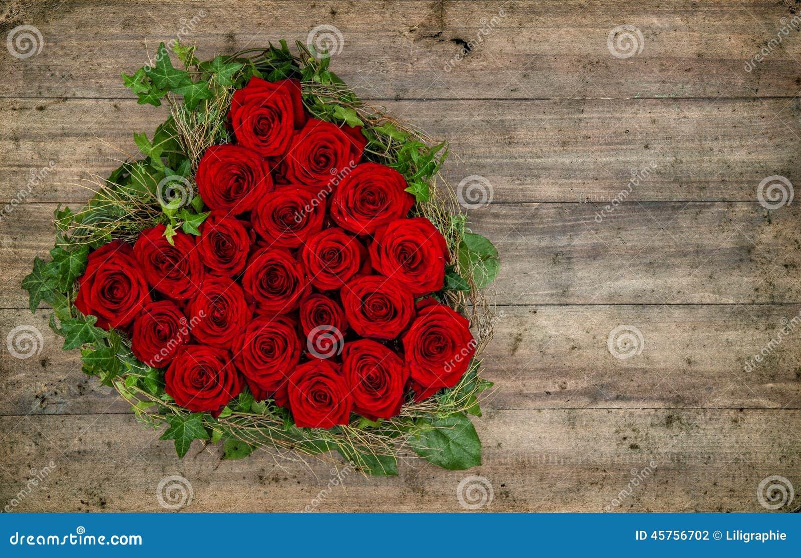 bouquet en forme de coeur de roses rouges sur le fond en bois