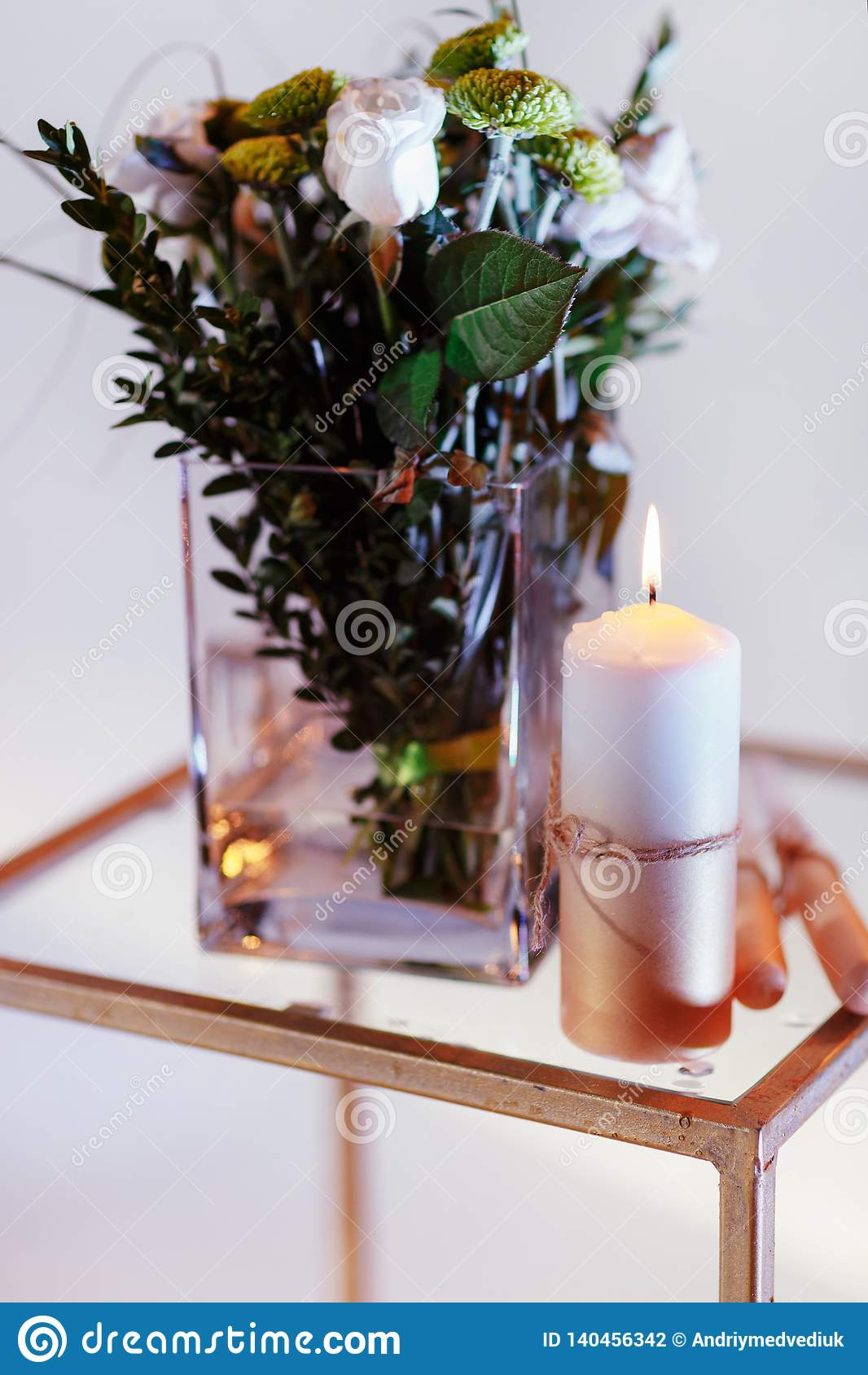 Bouquet of flowers in a vase, candles on a tray, vintage home decor on an a table
