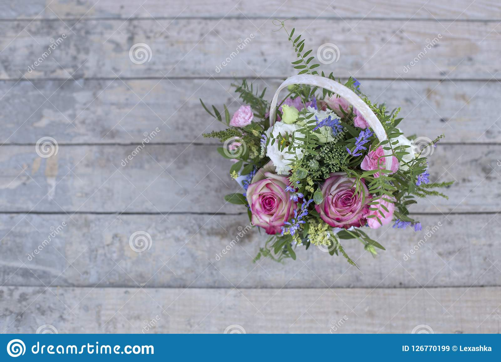 Bouquet of flowers in a white basket, top view. Bouquet of flowers in a white basket on a wooden background, top view Royalty Free Stock Images