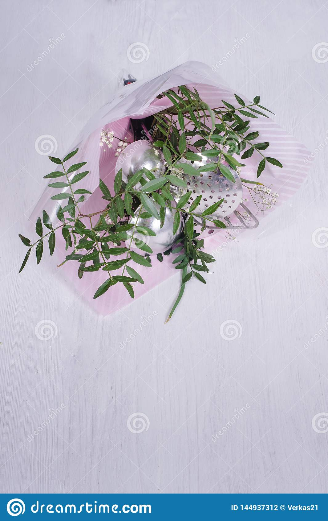 Bouquet of leaves and kitchen utensils.  gift-wrapped tools as symbol of patriarchal society and gender inequality. Sexism and