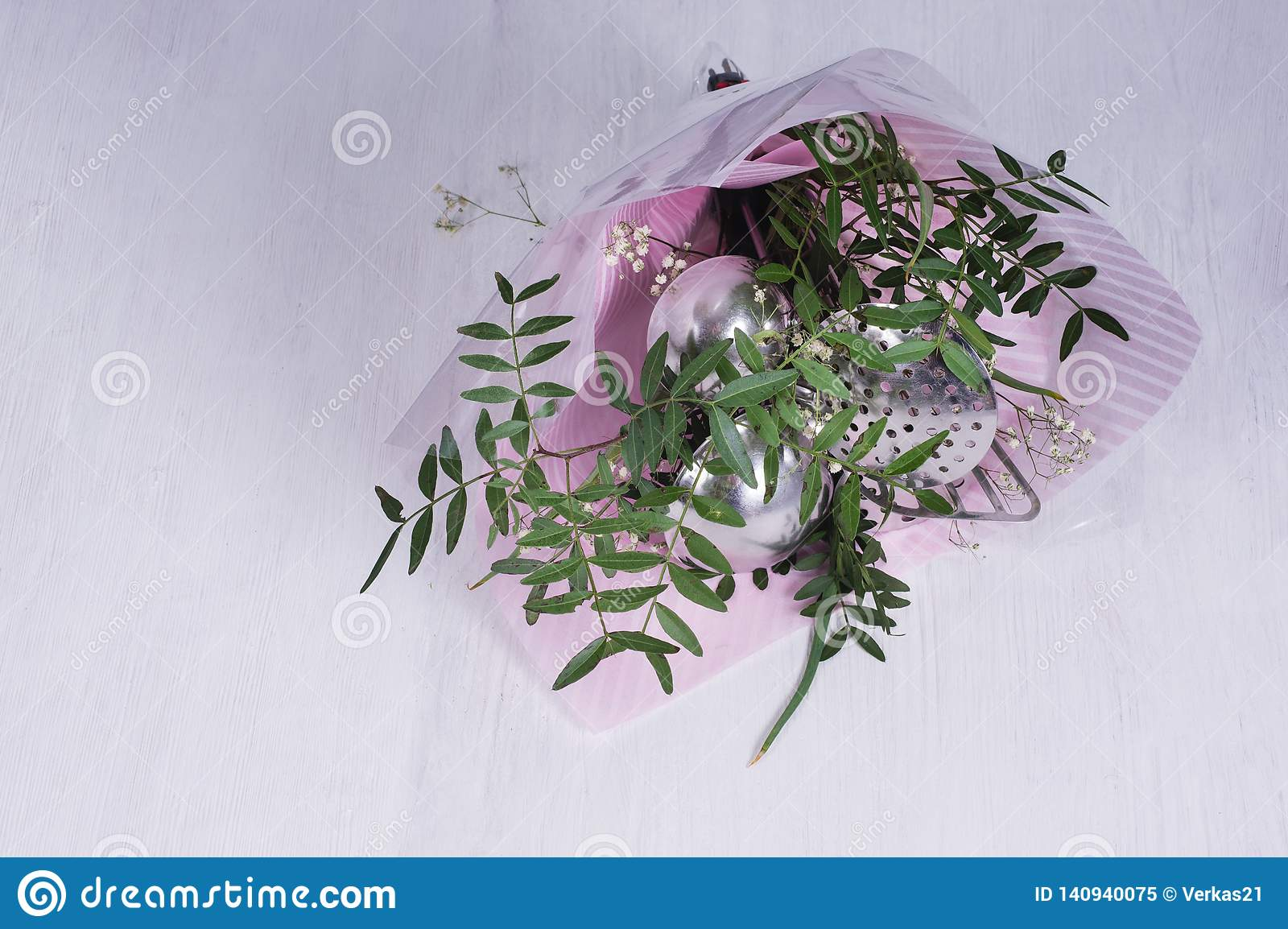 Bouquet of leaves and kitchen utensils. Set of gift-wrapped tools. concept of sexism and feminism, patriarchal society and gender