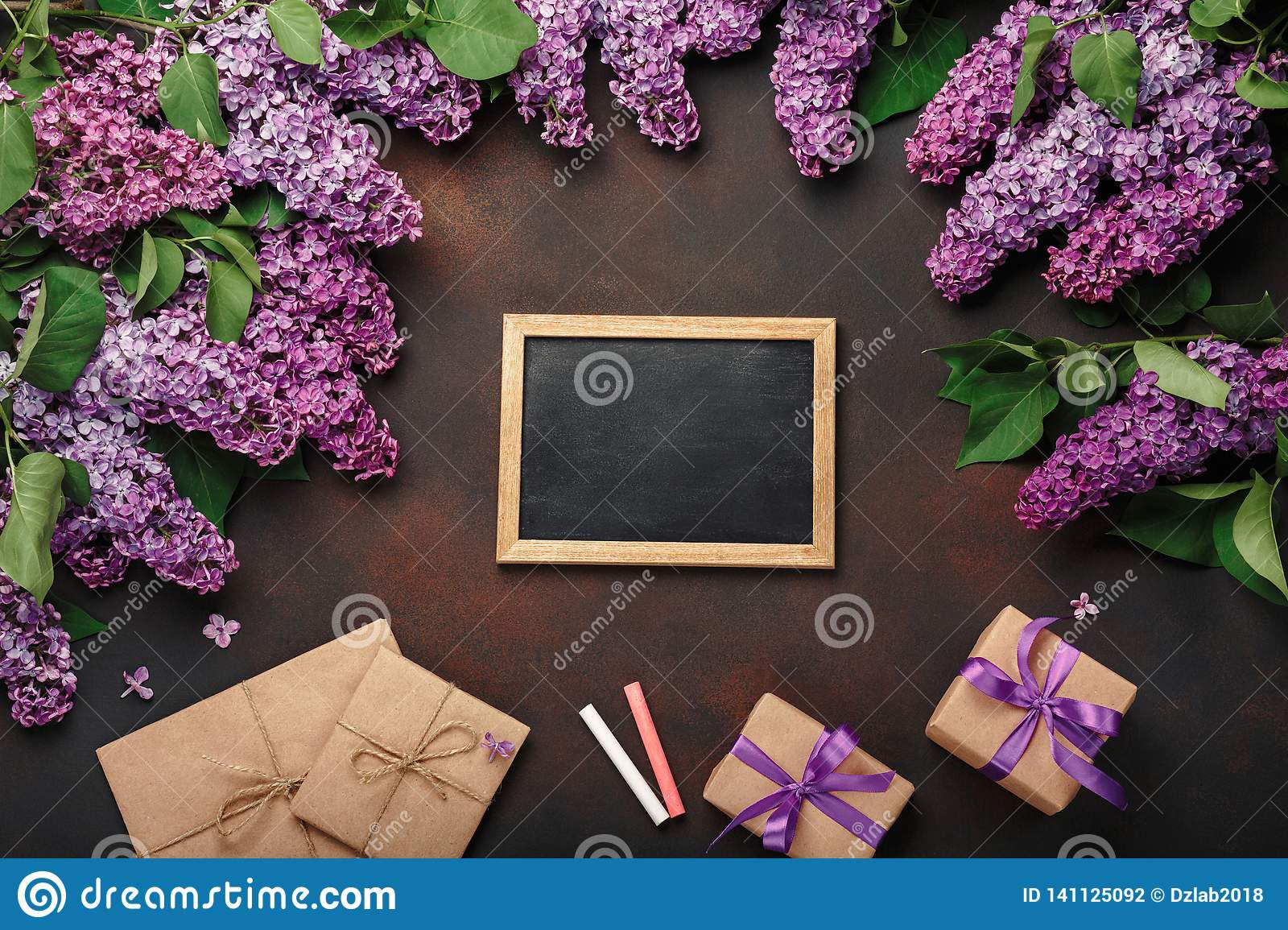 A bouquet of lilacs with chalk board, gift box, craft envelope on rusty background