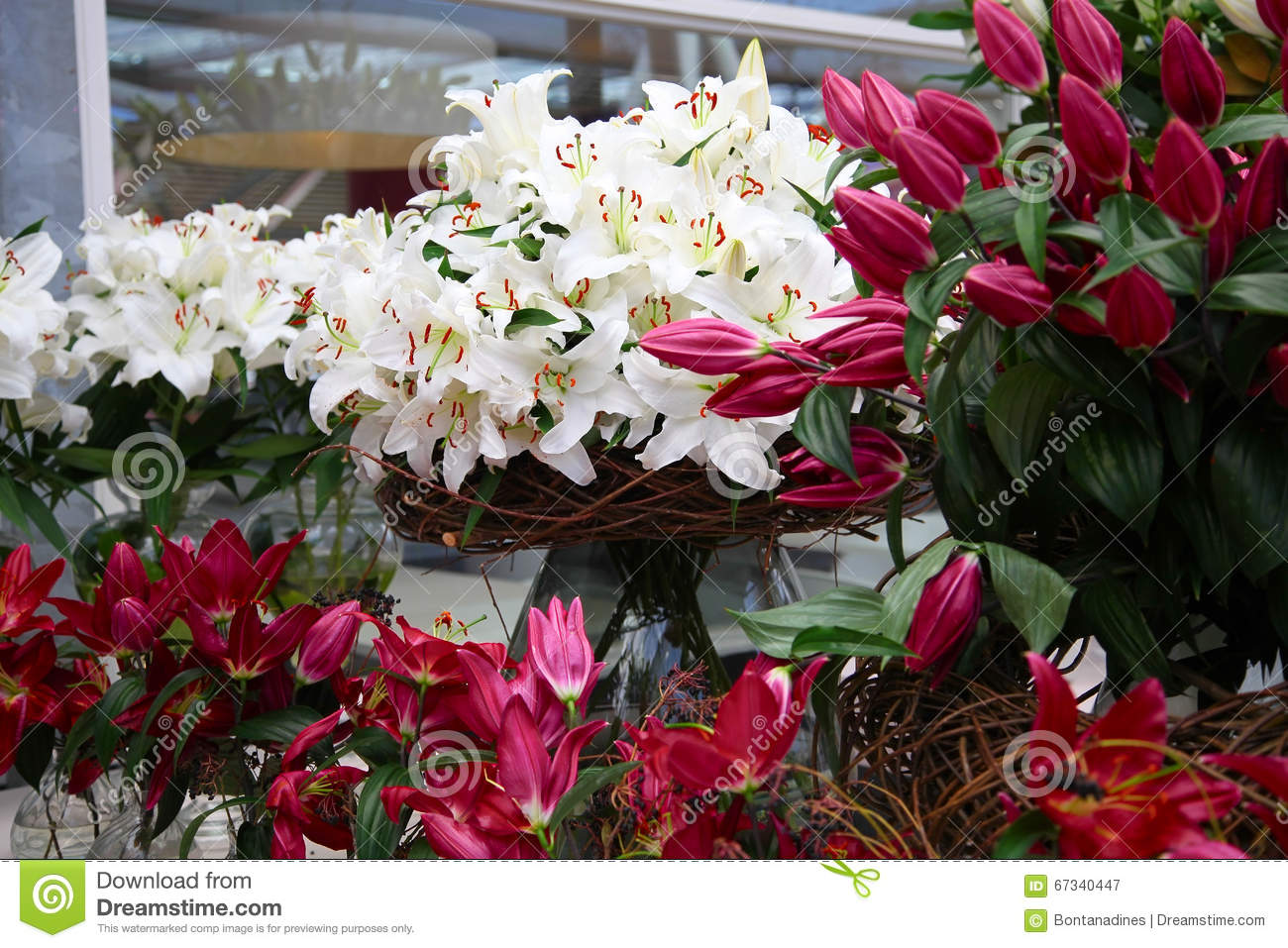 Bouquet Of Lilies In A Glass Vase With Wicker Basket In A Flower