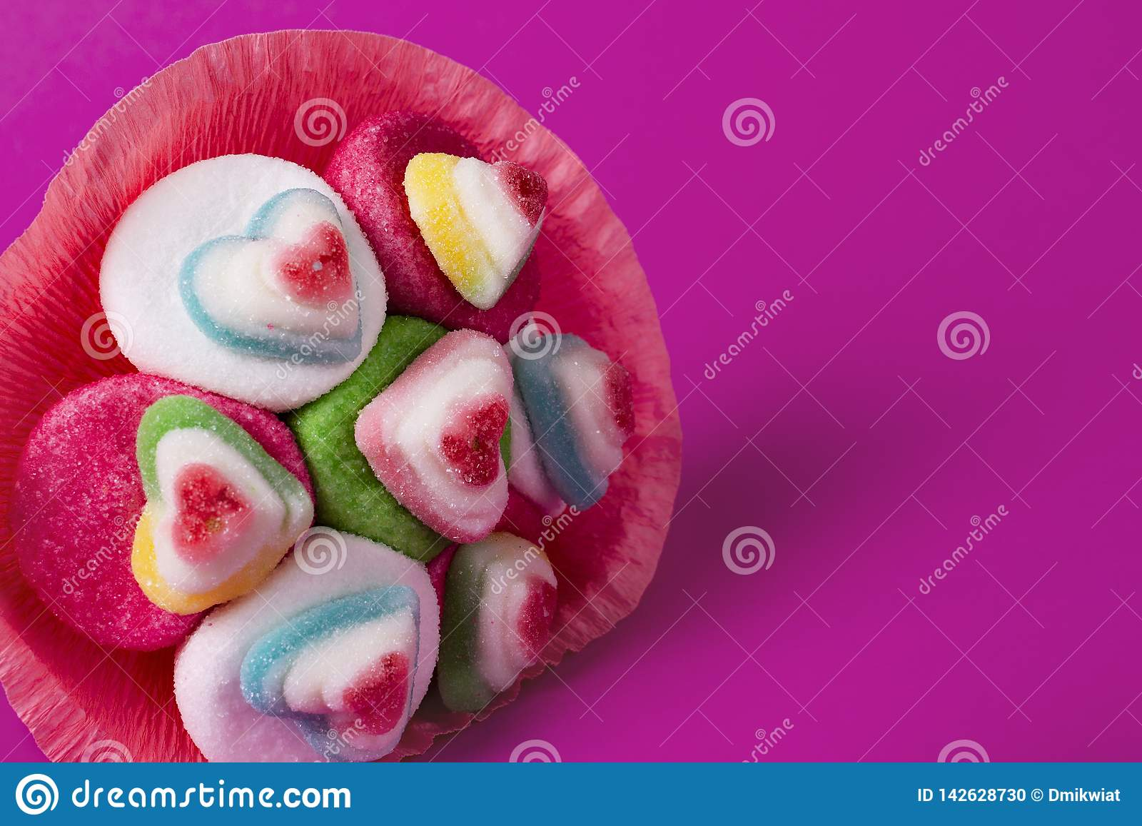 Bouquet of marmalade and sweets in pink packaging on a pink background