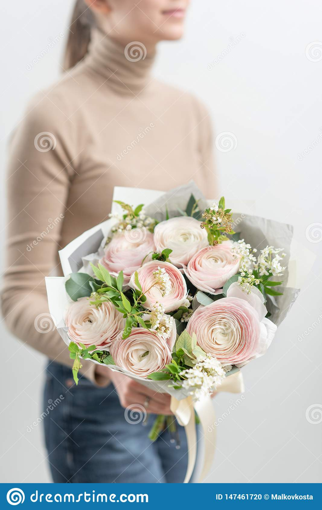 Bouquet mono des roses Bouquet sensible des fleurs m?lang?es chez les mains de la femme le travail du fleuriste ? un fleuriste