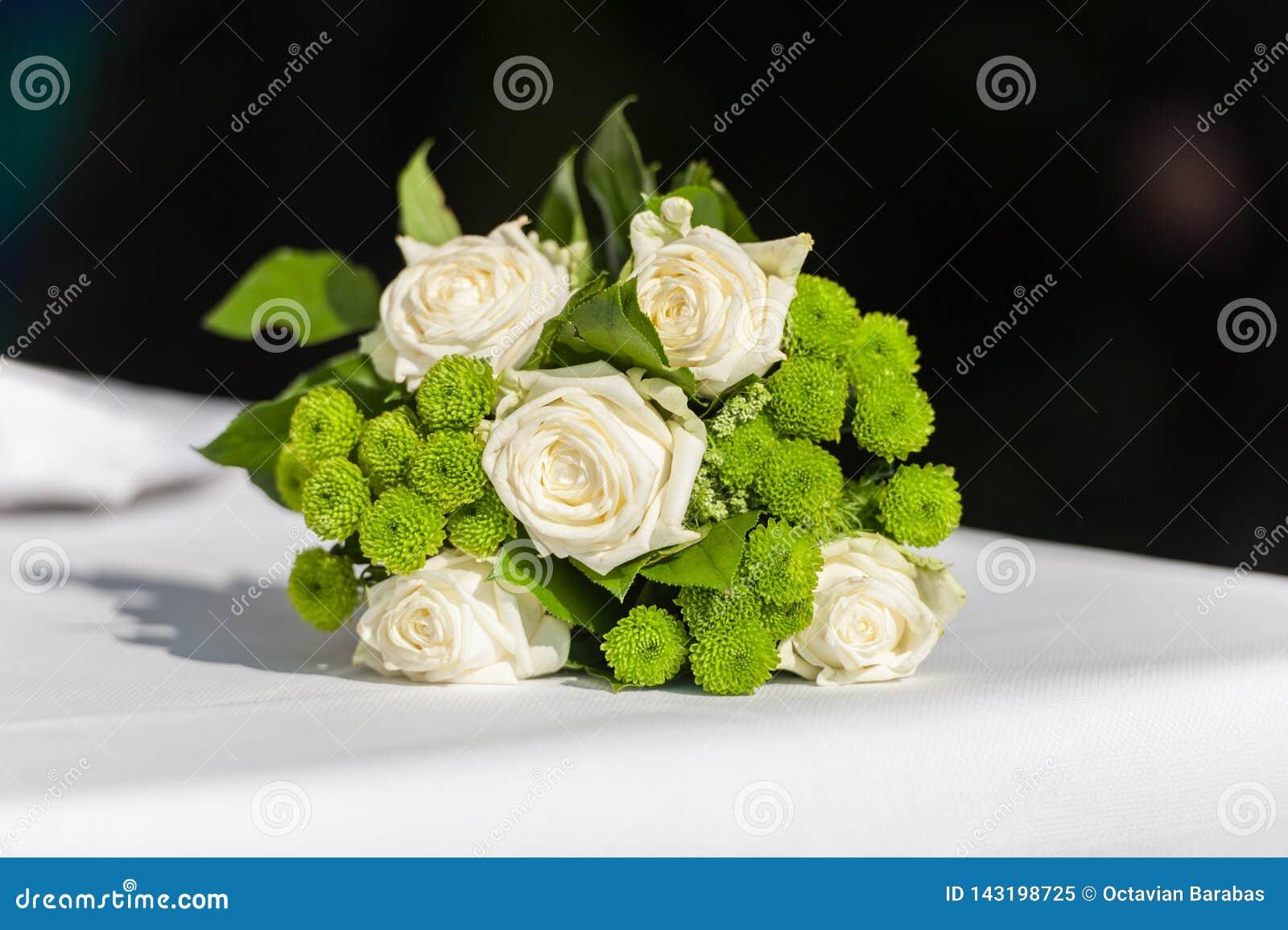 Bouquet nuptiale de fleur sur la table blanche sur le fond noir