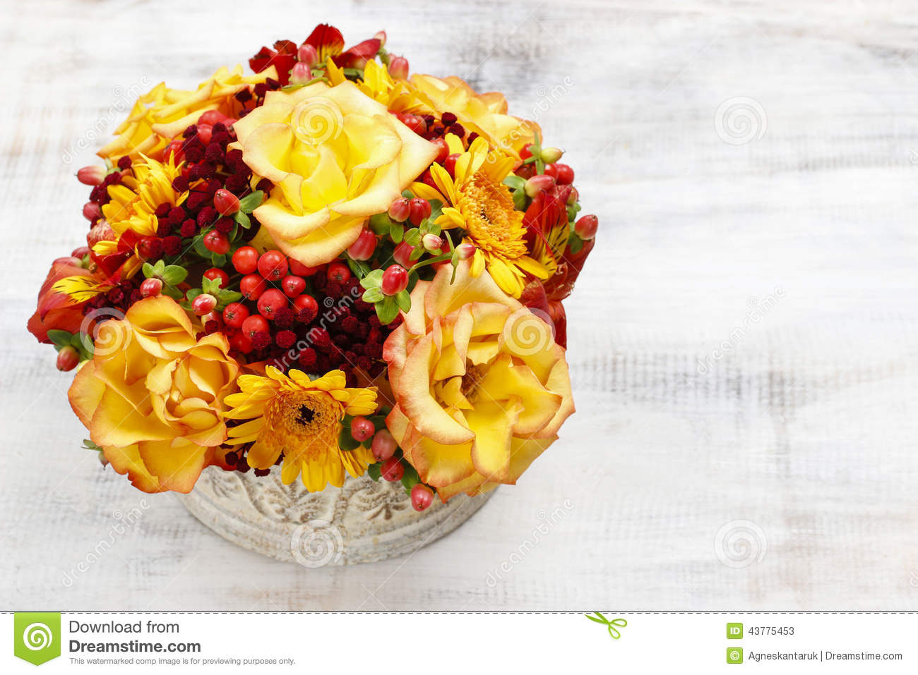Bouquet of orange roses and autumn plants in vintage ceramic vas