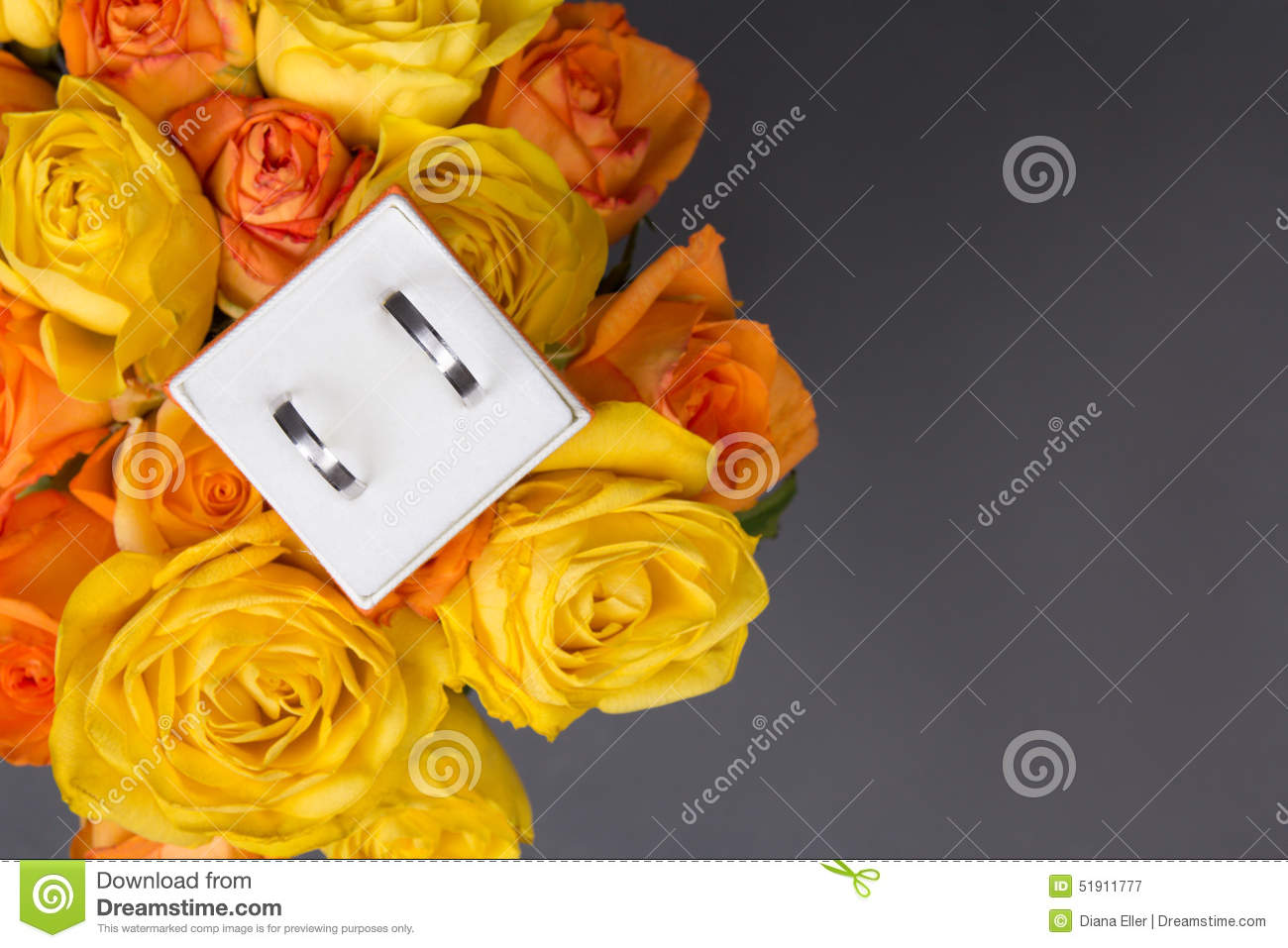 Bouquet Of Orange And Yellow Rose Flowers And Wedding Rings In G