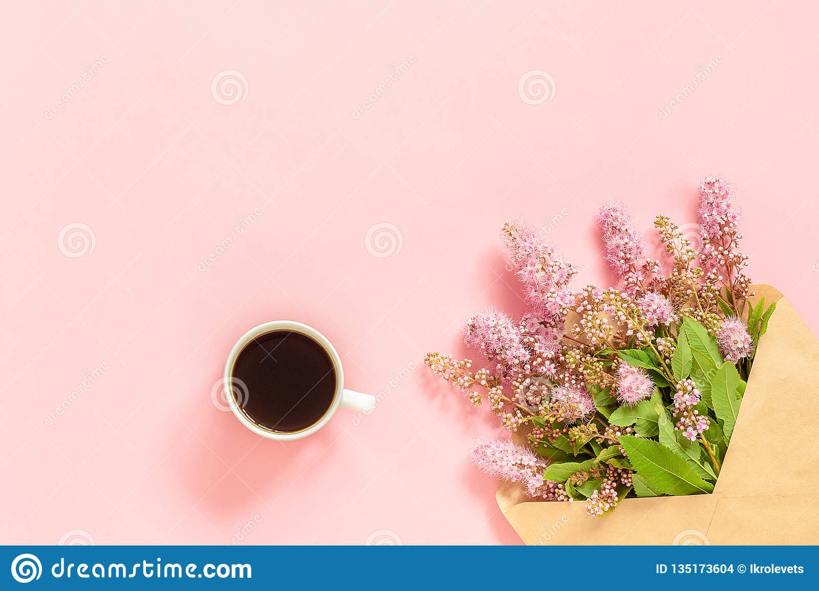 Bouquet of pink flowers in envelope, cup of coffee and a white blank card for text on pink background Concept Good morning or