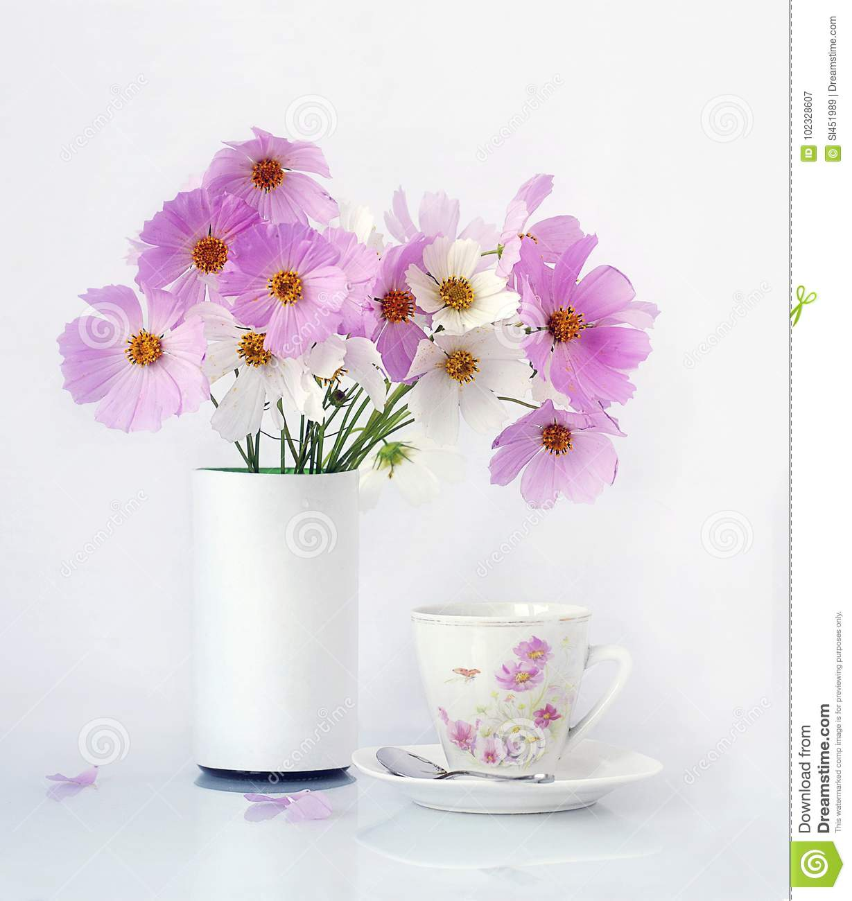 bouquet of pink flowers in a vase and a cup of coffee on a white