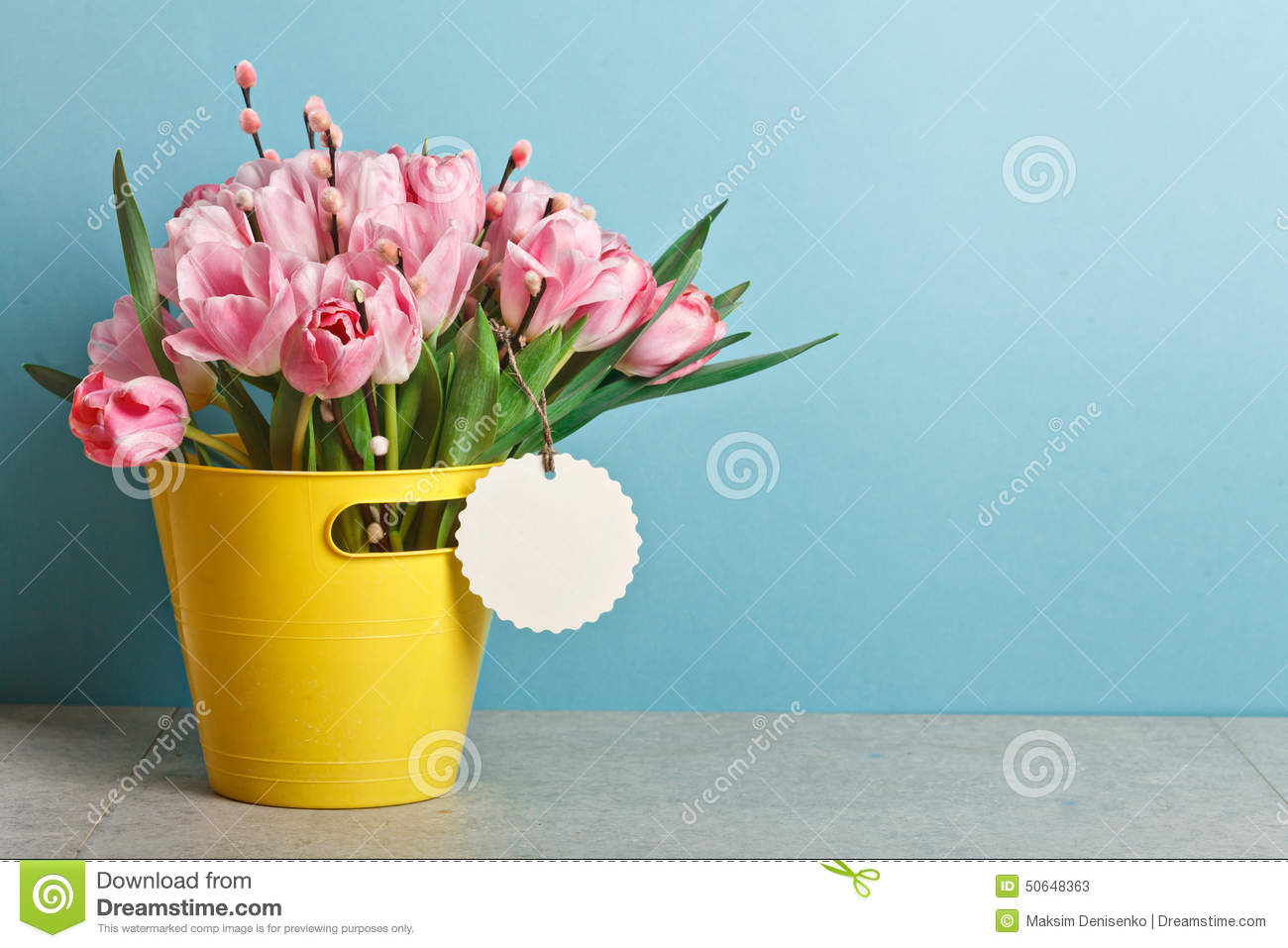 Bouquet of pink fresh tulips with pussy-willow in yellow bucket