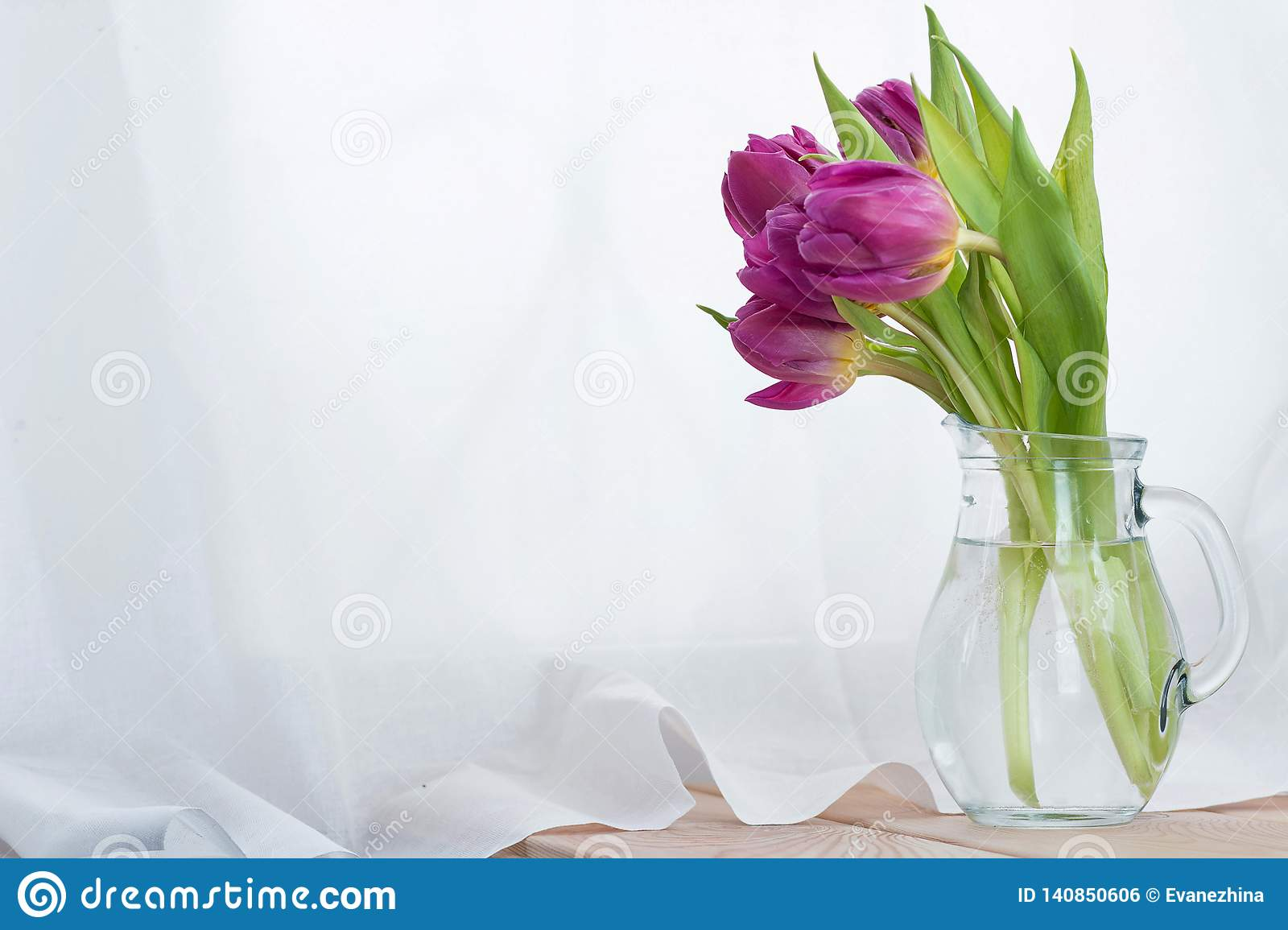 The bouquet of pink tulips in a glass decanter on a wooden table