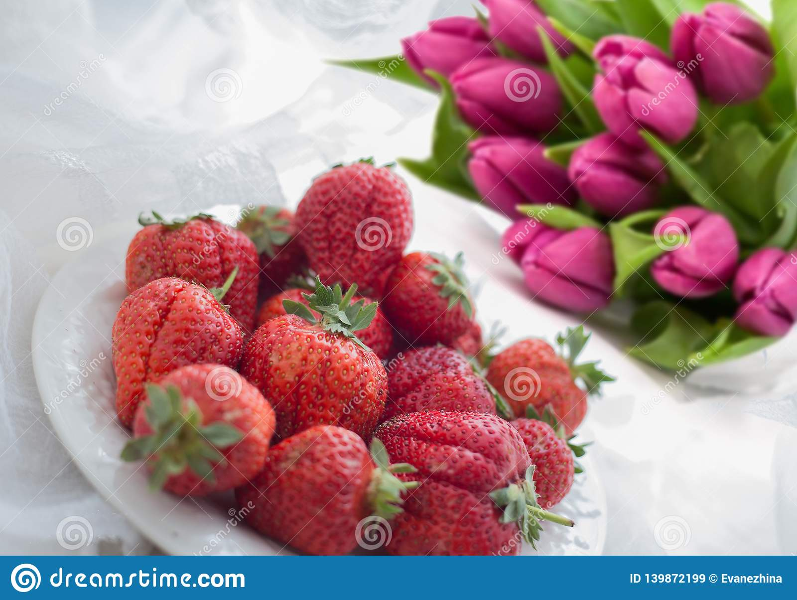 Bouquet of pink tulips and strawberry. A gift for March 8