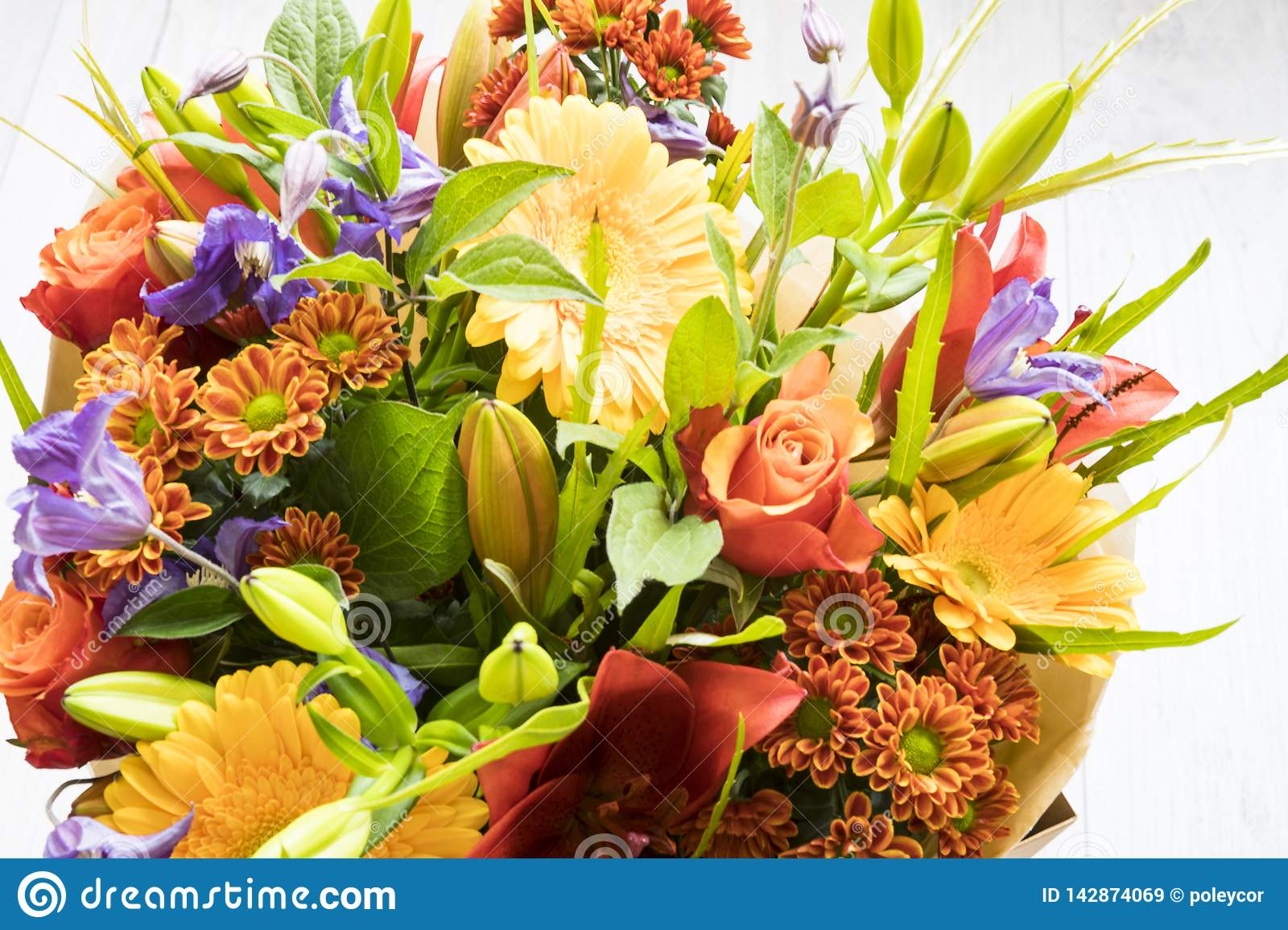 Bouquet with roses, red lily,  gerbera, dahlia and leaves.
