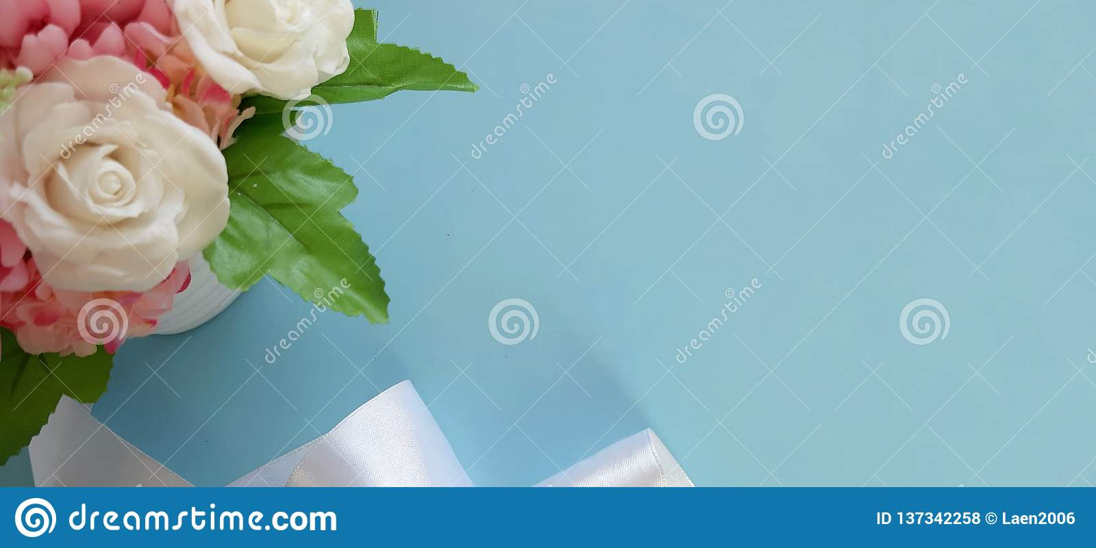 Bouquet of roses, silk ribbon on blue background.