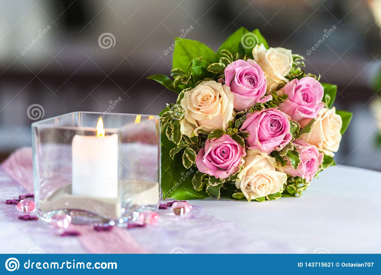 Bouquet of roses on table with candle