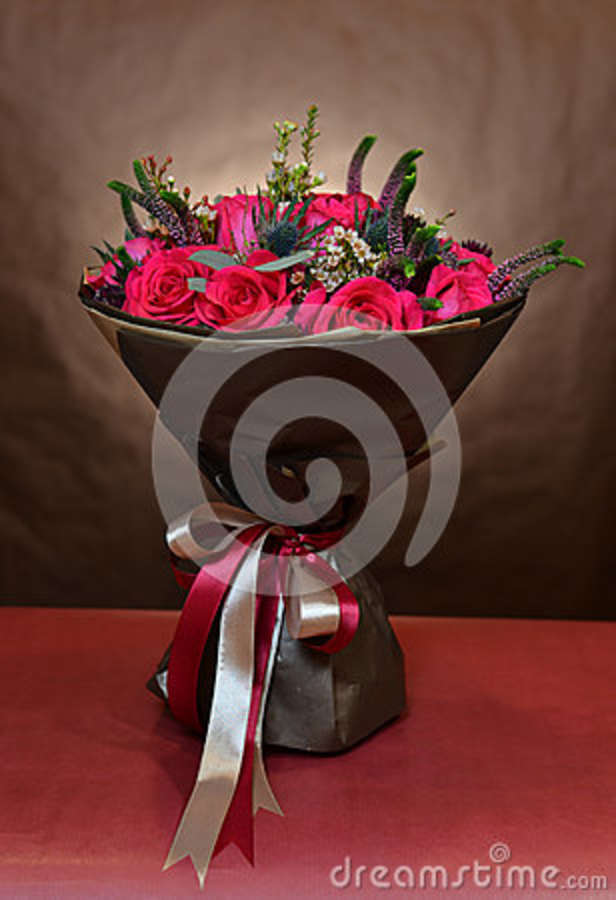 Bouquet Of Roses Wrapped In Brown Paper And Tied With Ribbons Stock