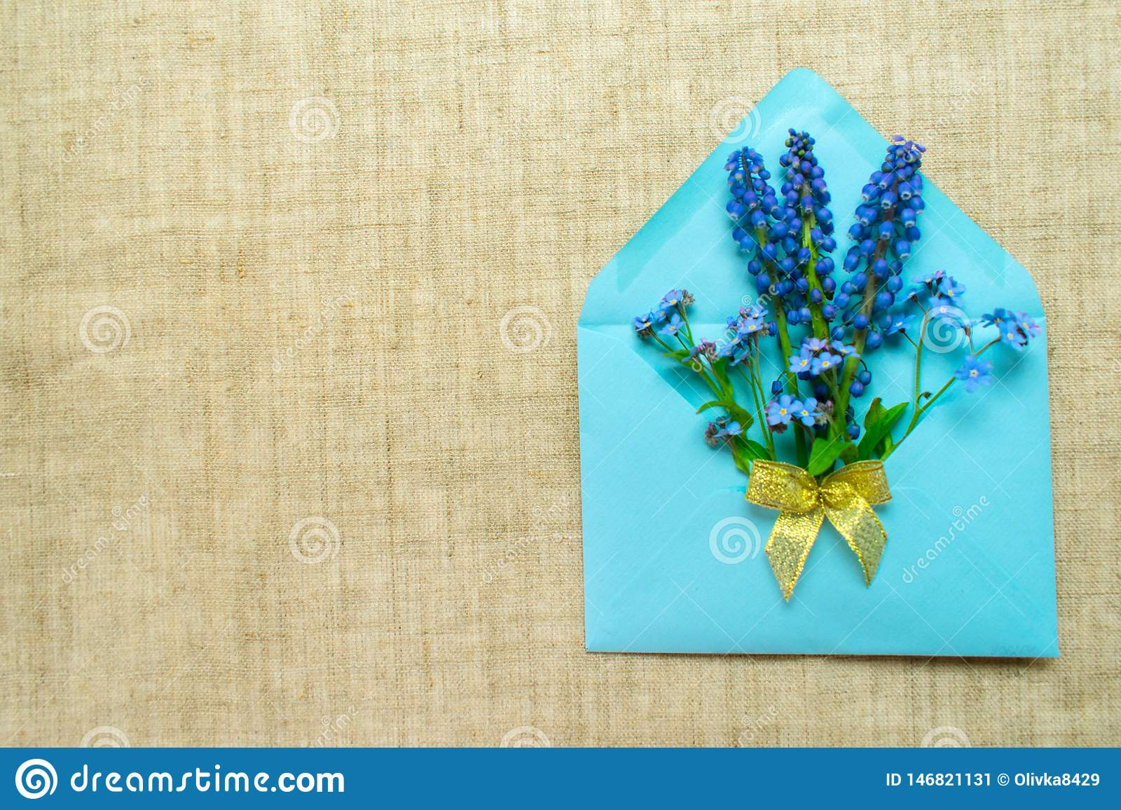 A bouquet of small blue flowers in a blue envelope decorated with a golden bow on a tablecloth made of natural flax.