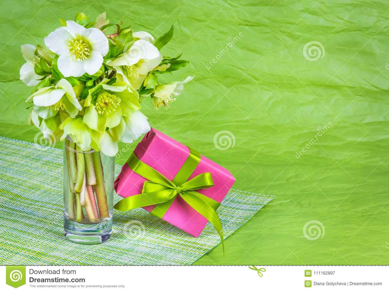 Bouquet of spring flowers and box with gift on green background. Bouquet of  hellebells. e0e802a42d