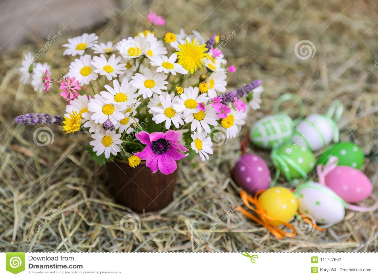 A Bouquet Of Spring Flowers And Decorated Easter Eggs On The Hay