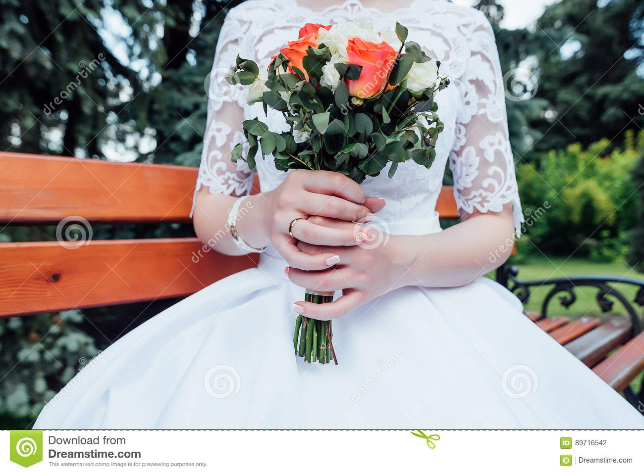 A bouquet of white and coral roses in the bride`s hands