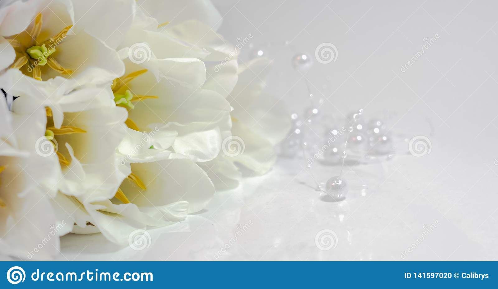 Bouquet of white tulips with white beads on a white table