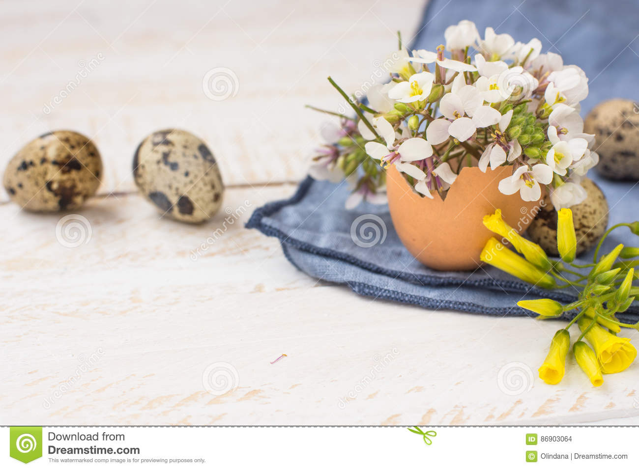 Bouquet of white yellow flowers in eggshell, quail eggs, blue napkin on wood table, Easter interior decoration