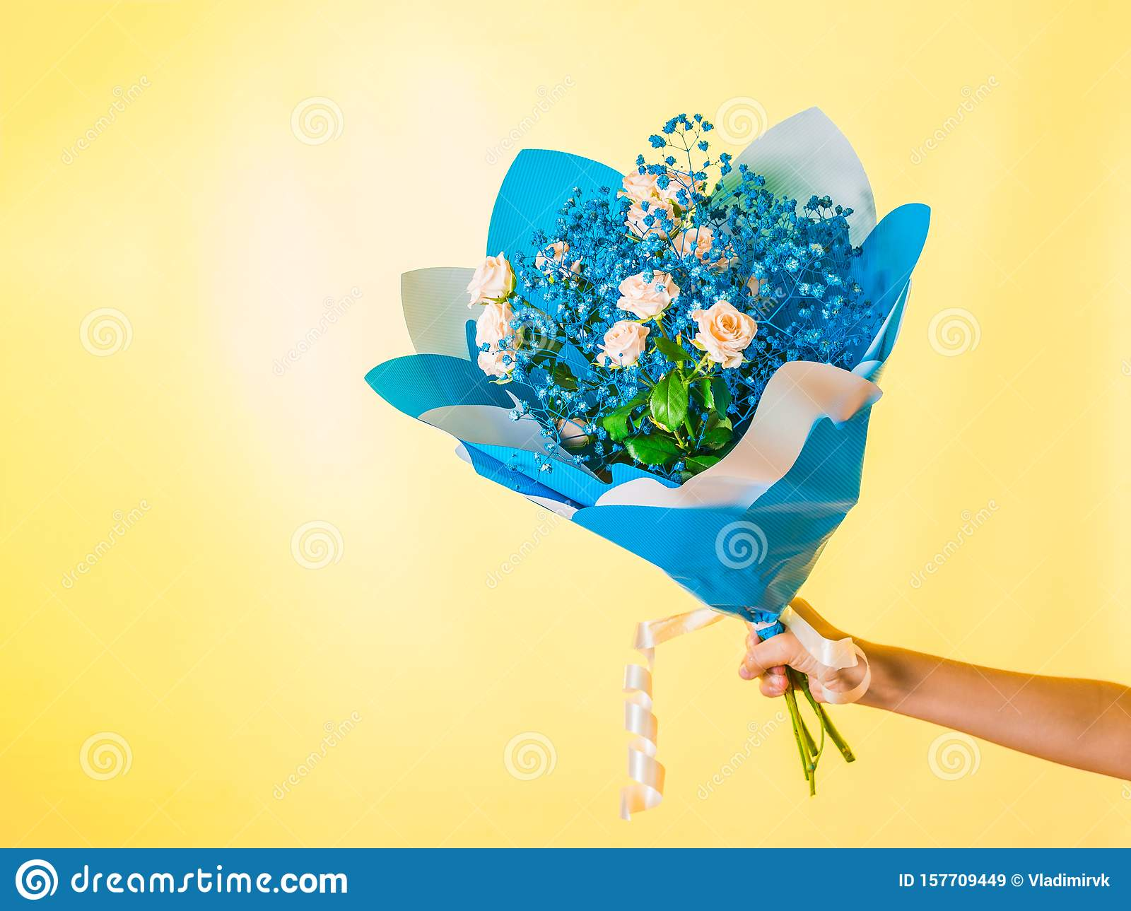 Bouquet With Yellow Roses And Small Blue Flowers In Hand On A Yellow Background A Gift For A Woman Space For Your Text Stock Image Image Of Blossom Bulb 157709449