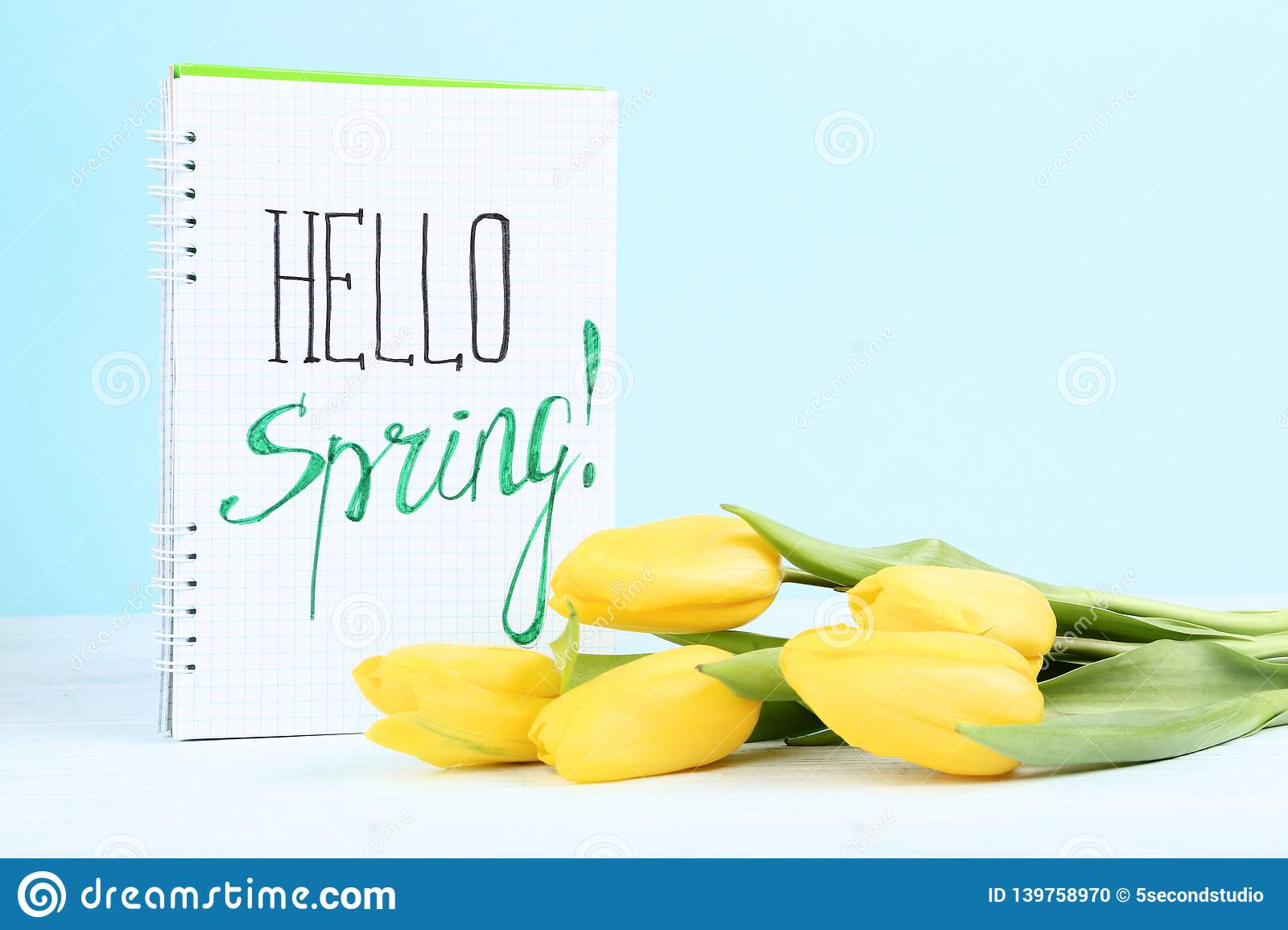 Bouquet of yellow tulips with notepad and text Hello Spring stock photo