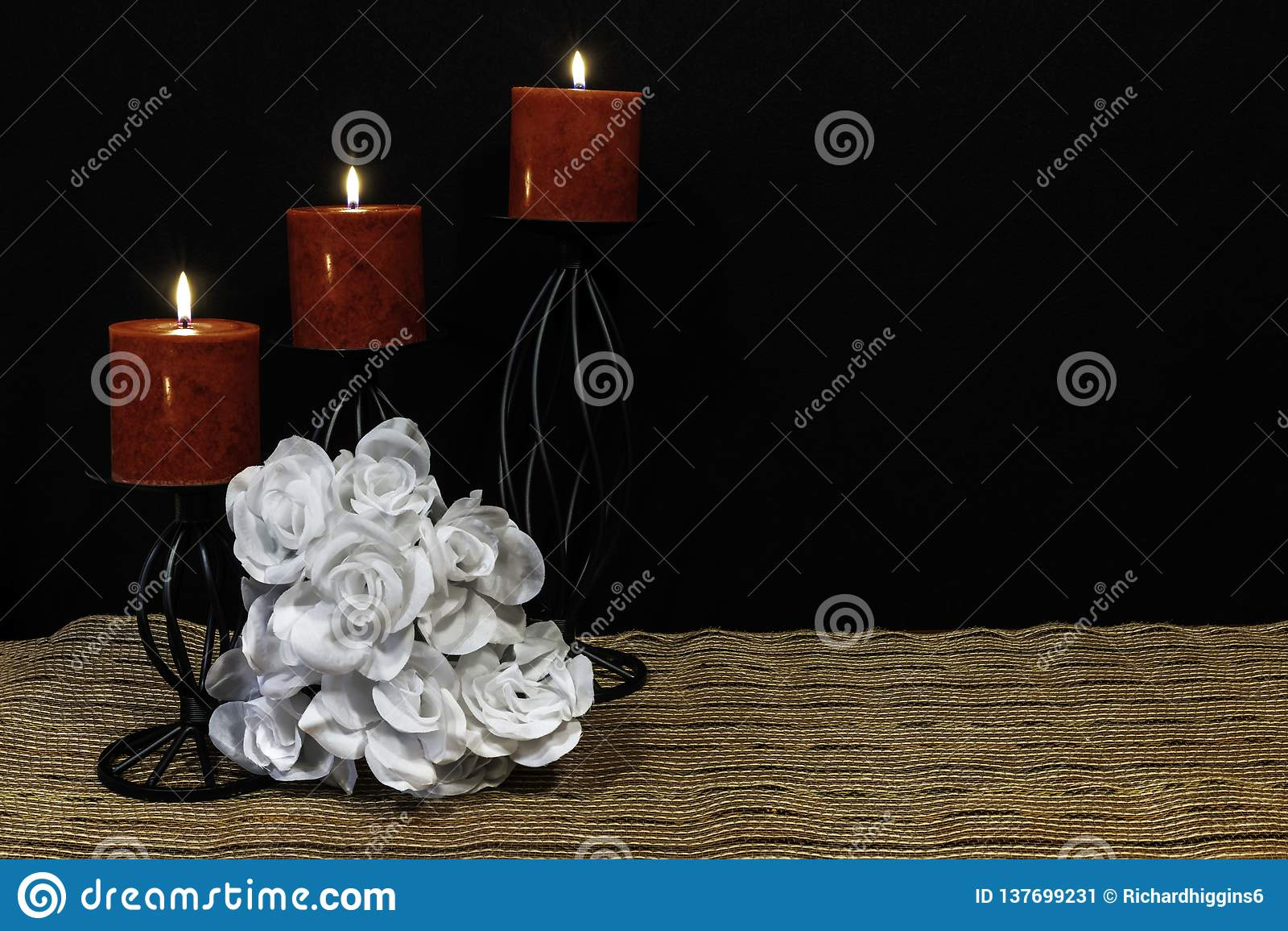 Bouquie hermoso de las rosas blancas, de las velas rojas encaramadas en candeleros negros en la estera de lugar de la malla y la