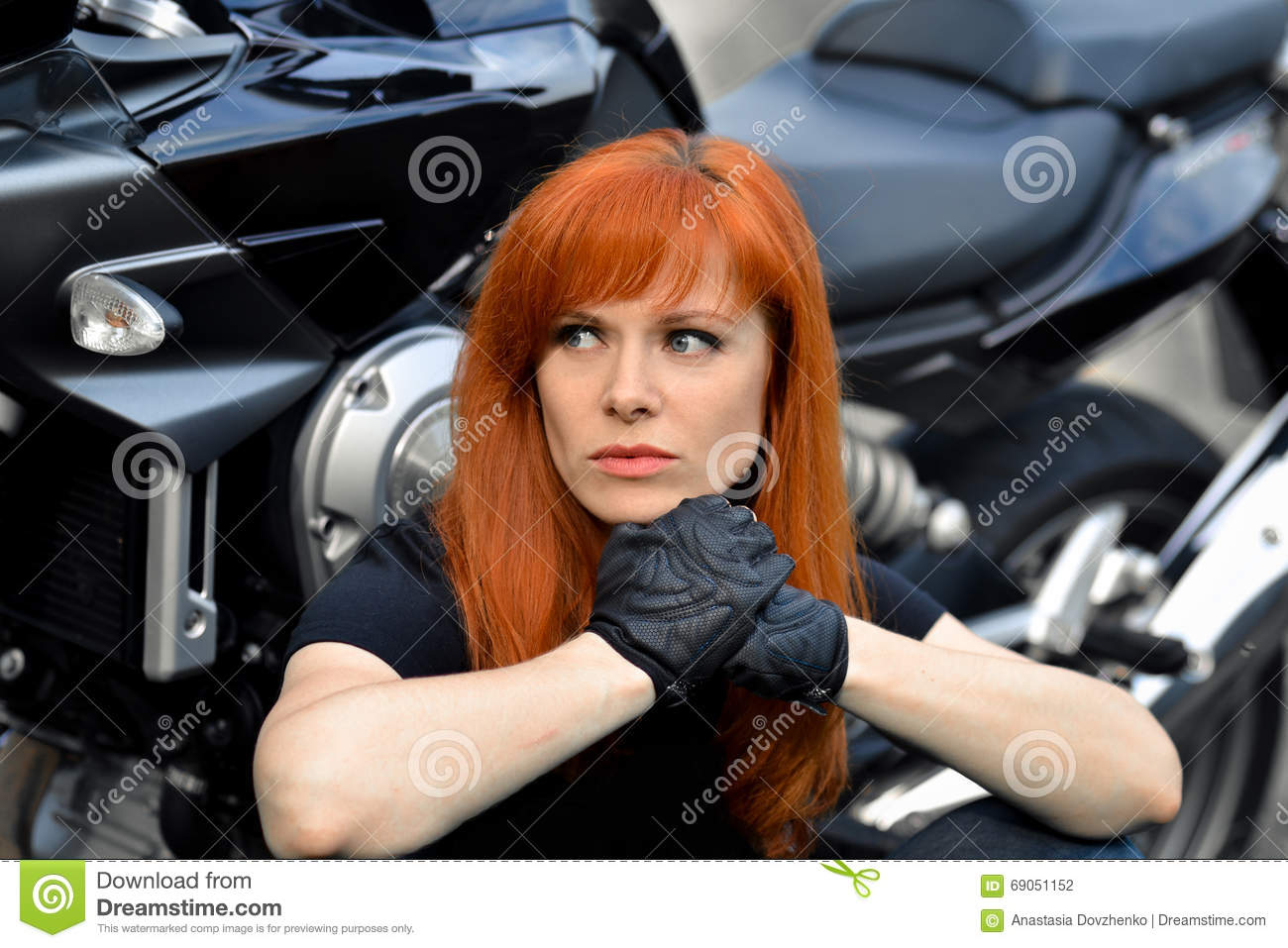 Serious,powerful,thinking leader of bikers sit near the bike