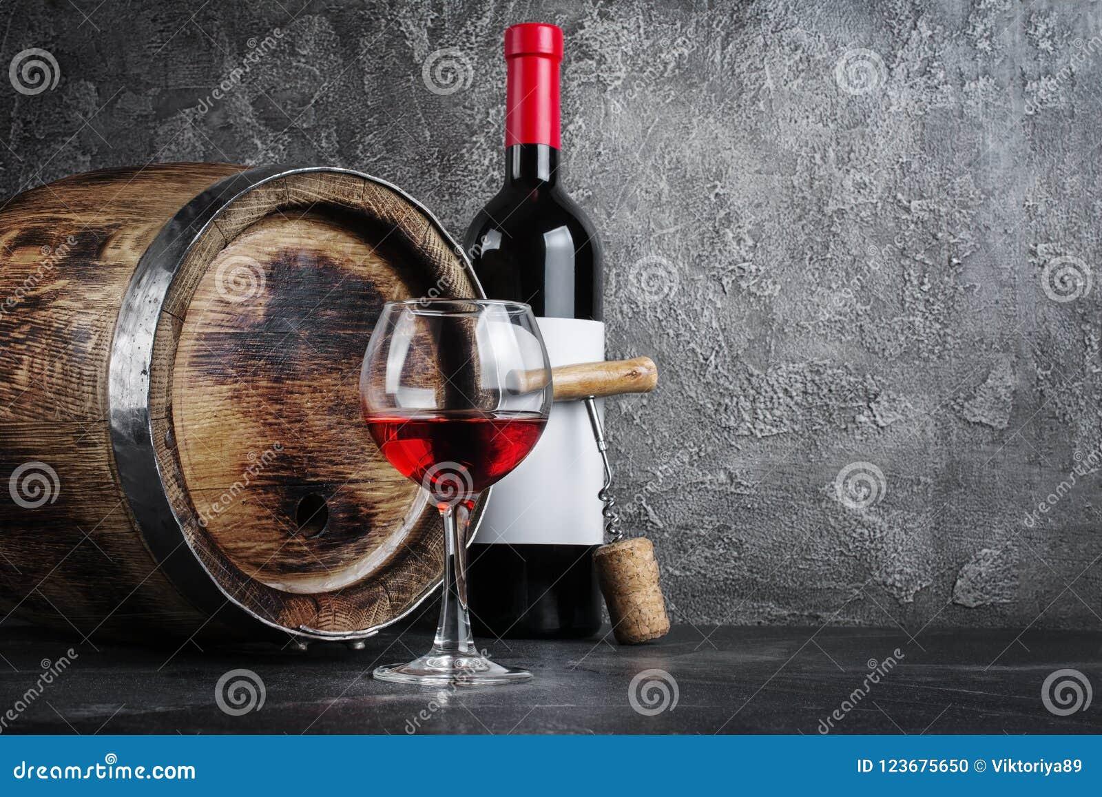 Bouteille de vin rouge avec le verre pour goûter et baril en bois dans la cave foncée
