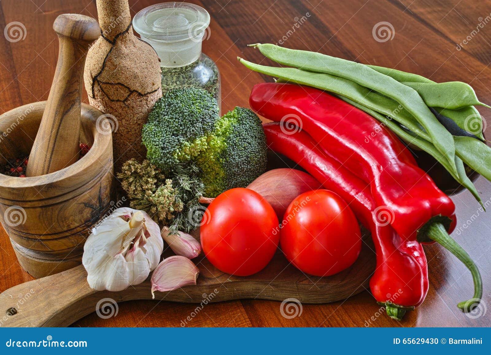 Bouteille en verre avec des épices, bouteille de liège, légumes de mortier, rouges et verts en bois olives, brocoli, tomates, ail