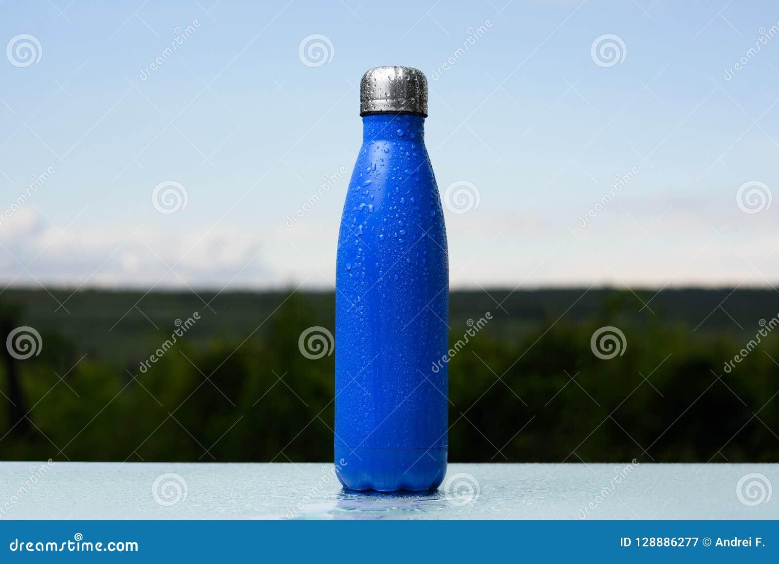 Bouteille inoxydable thermo, pulvérisée avec de l eau Ciel et forêt sur le fond Sur le bureau en verre Thermos de couleur bleue m