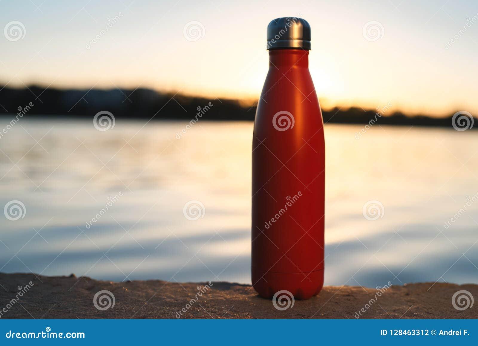 Bouteille thermo rouge inoxydable pour l eau Coucher du soleil et eau sur le fond